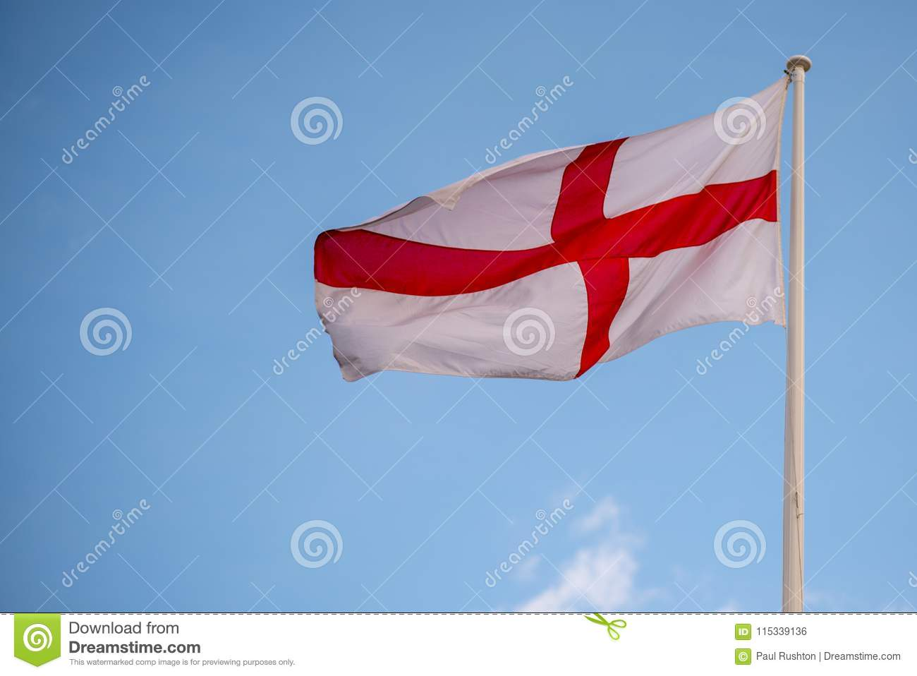 89665228 National flag of England St Georges flag blowing in the wind with blue sky  in background