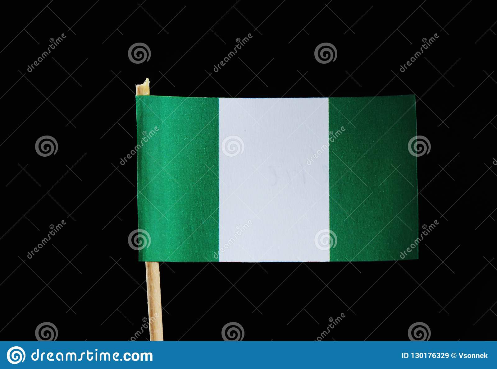 A national flag of Nigeria on toothpick on black background. Nigerian flag contain green and white colour.