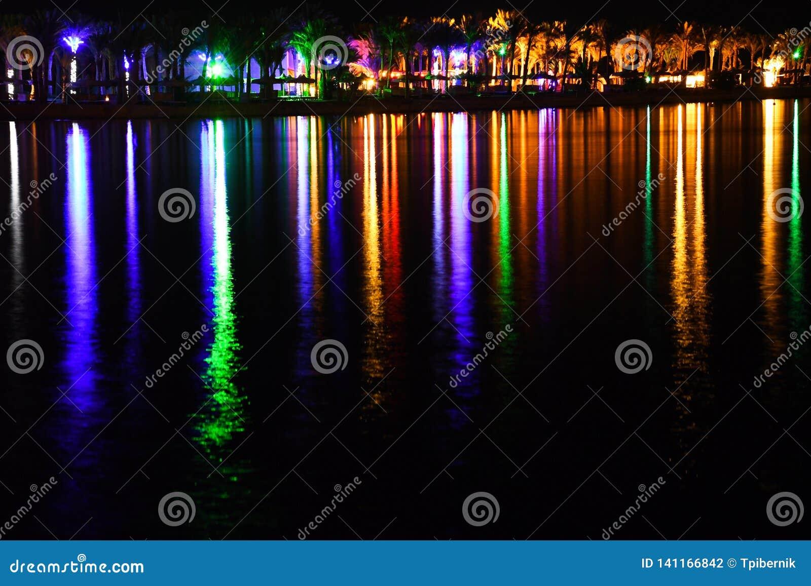 Nattblixt och skinande strand med färgrika ljus och härlig lång reflexion