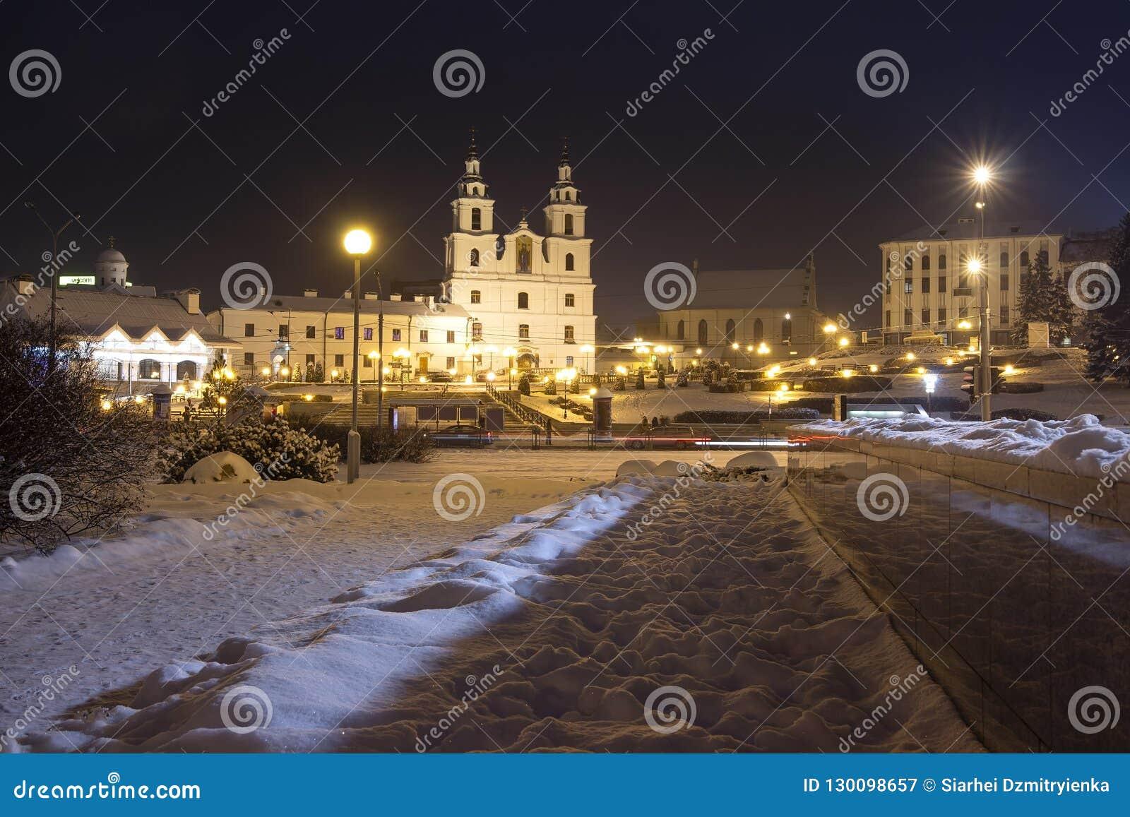 Nattcityscape av vintern Minsk Berömd yttersida i aftonen Minsk, Vitryssland Domkyrka för helig ande på central fyrkant