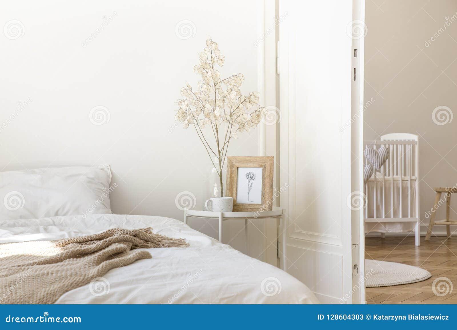 Nattduksbordet för vit metall med kaffe rånar, fattar i den glass vasen och enkel affisch i ramen som förläggas av sängen