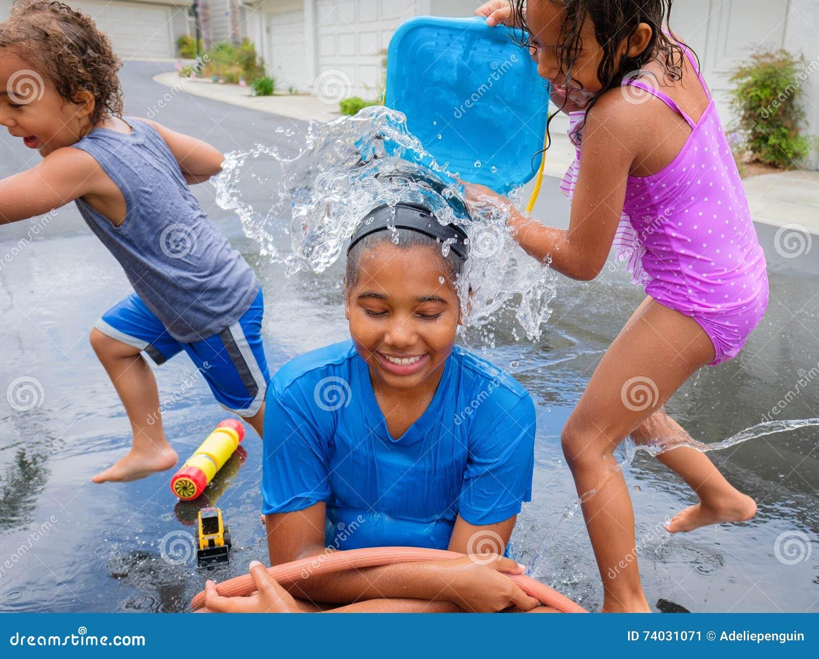 Natte Broer En Zusters Die Buiten Met Water Spelen Stock Afbeelding