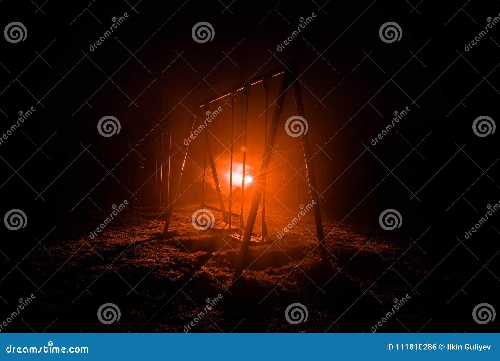 Nattfoto av metallgunga som står utomhus- på nattetid med dimma och overkligt tonat ljus på bakgrund Inget där