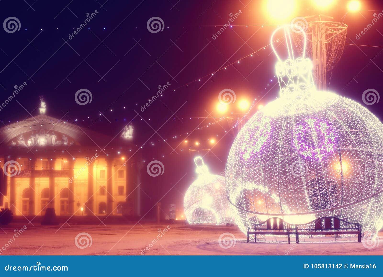 Nattplats med upplysta den julbollar och teatern