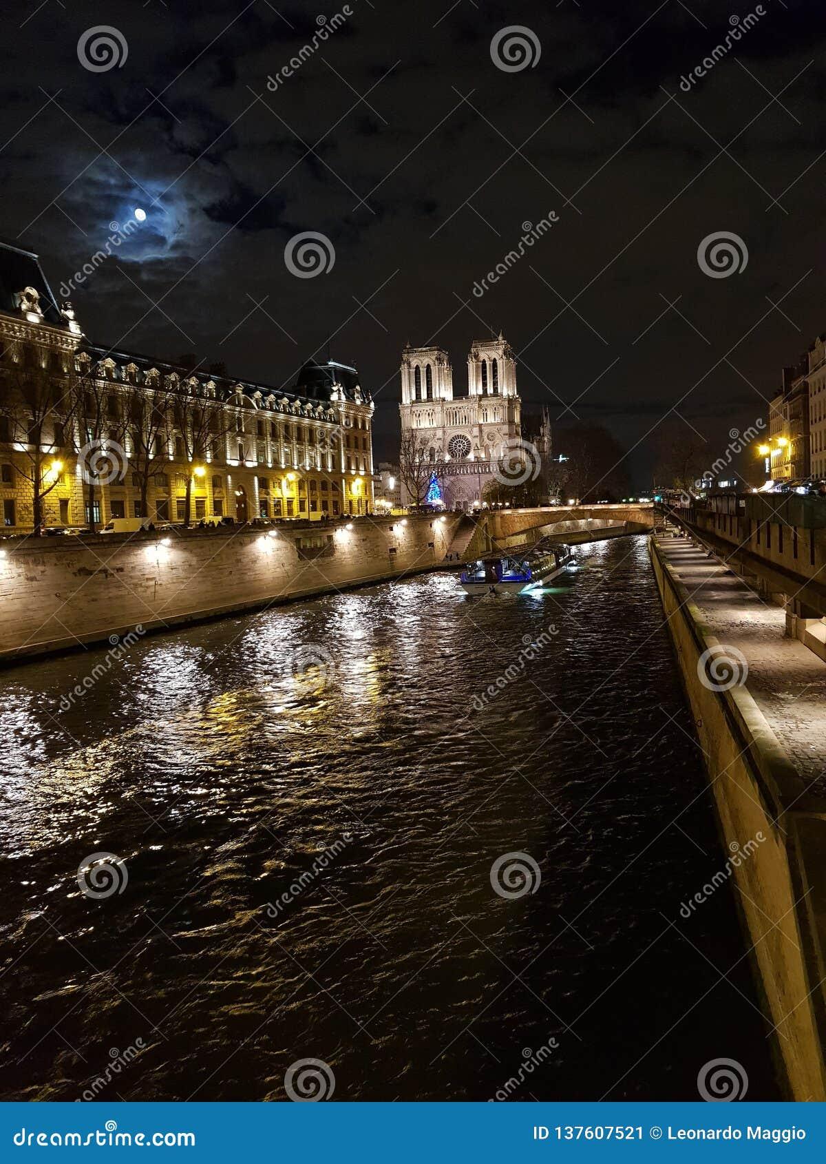 Nattsikt av Seinet River med Notren Dame Cathedral i bakgrunden