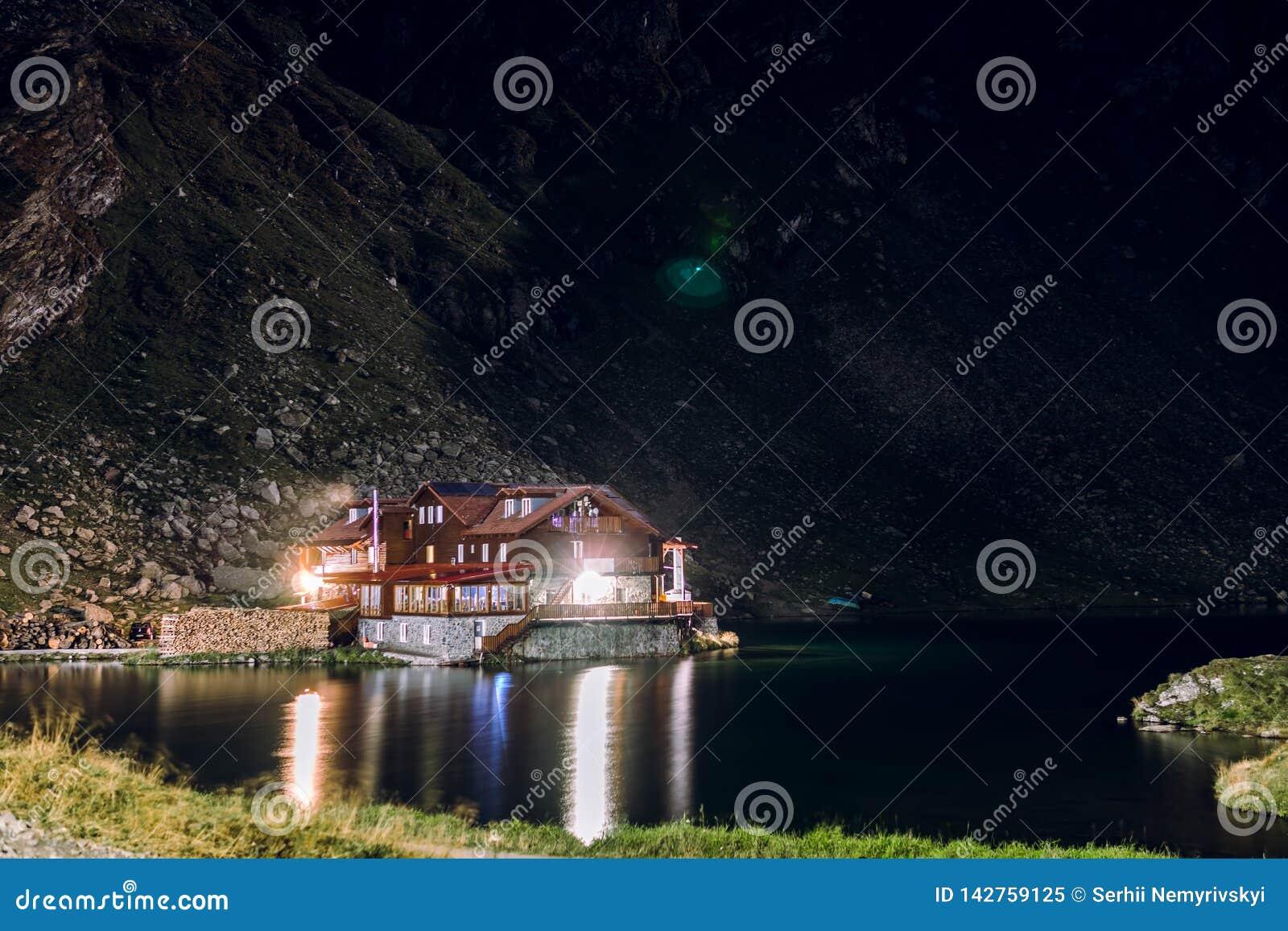 Nattsikt på hus, hotell på kusten av en bergsjö, Balea gummilacka, turism- och semesterbegrepp, lopp och aktiv livsstil,