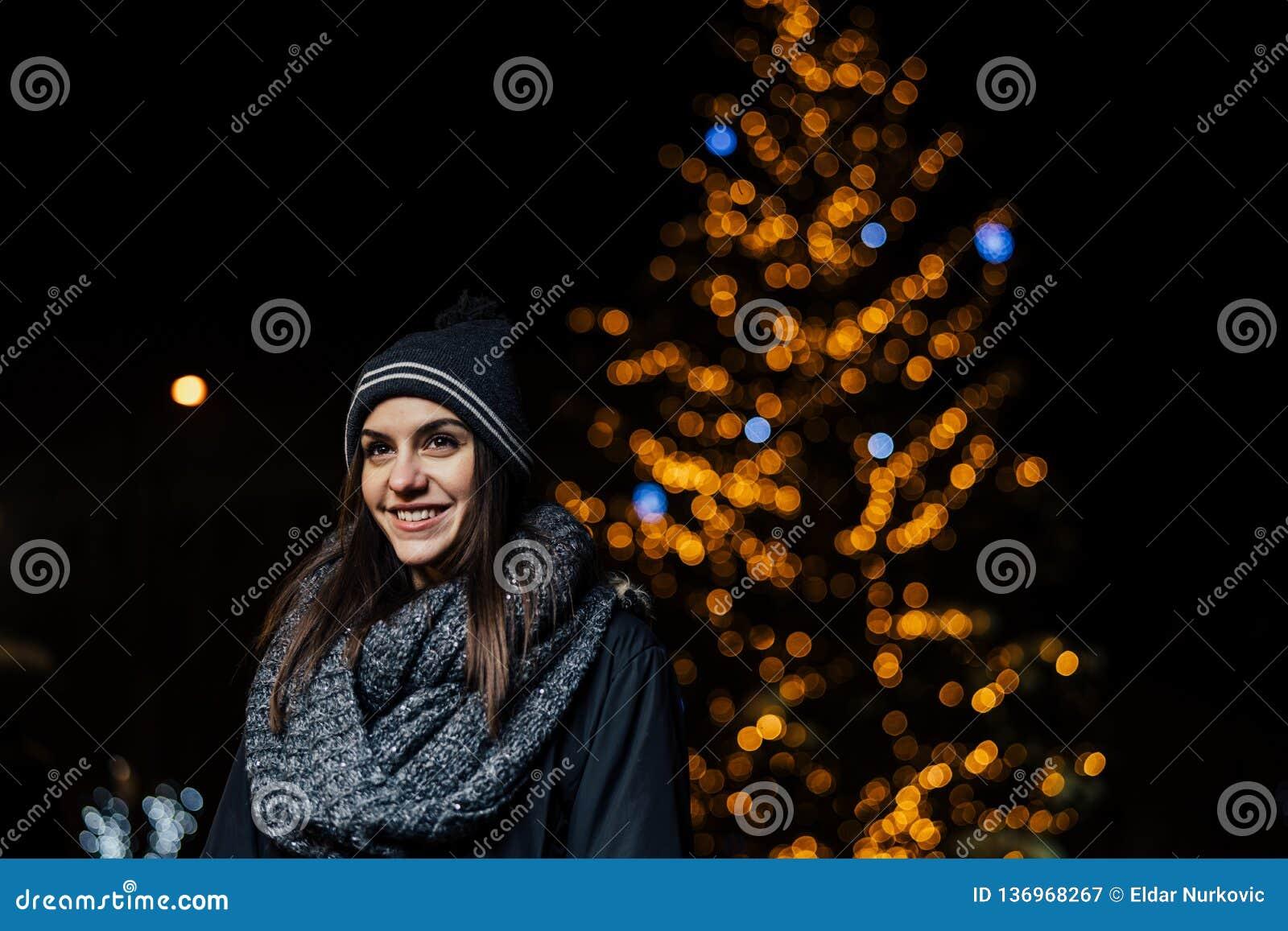 Nattståenden av en härlig brunettkvinna som ler tycka om vinter parkerar in Vinterglädje vinter för snow för pojkeferielay positi