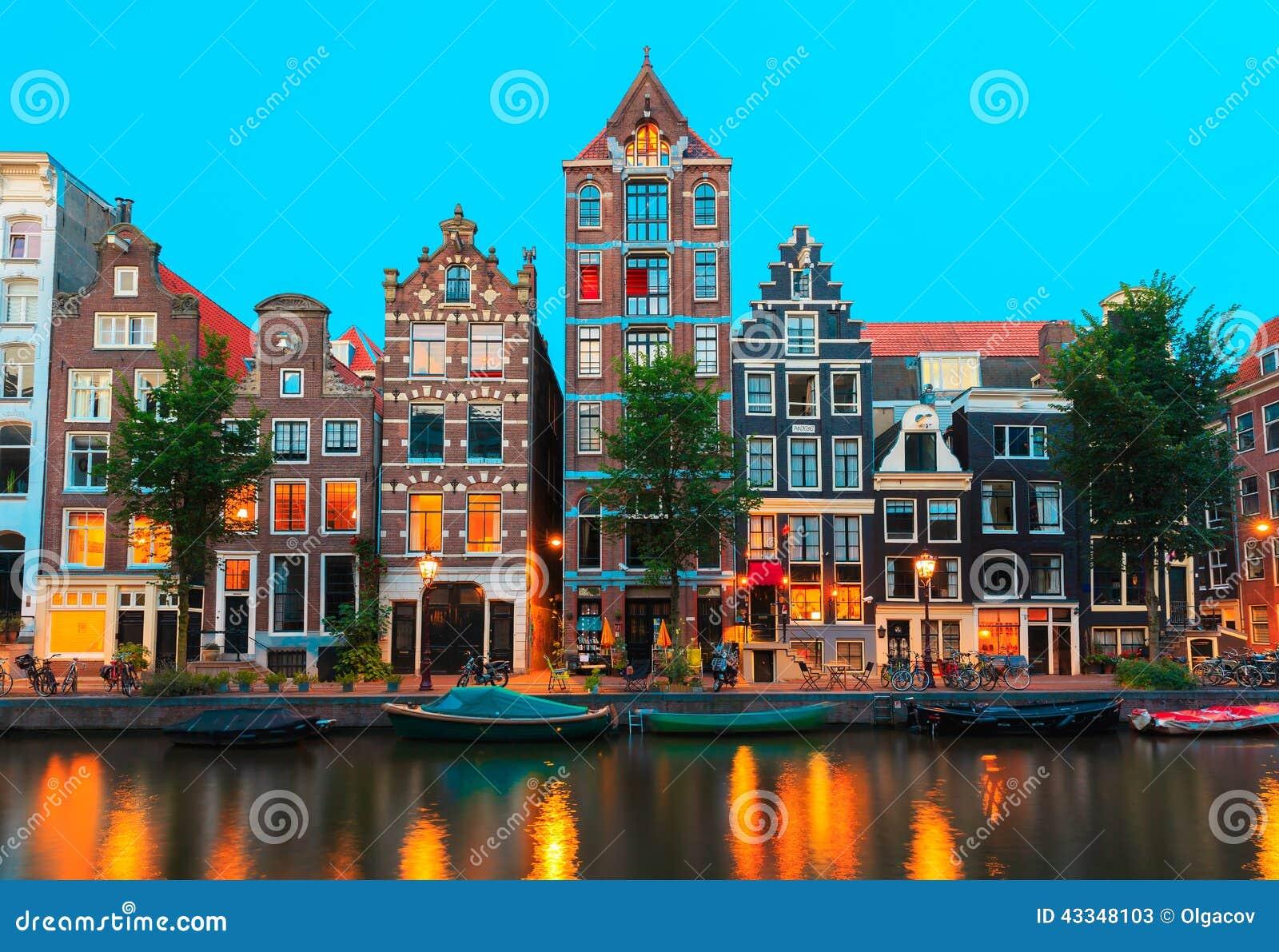 Nattstadssikt av Amsterdam kanaler och typisk ho