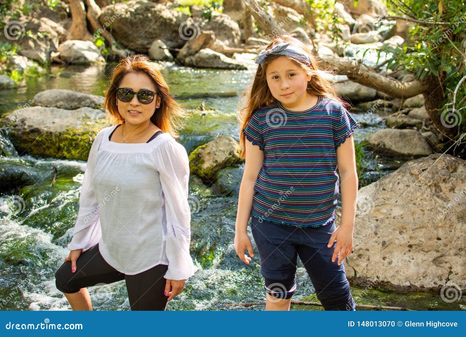 Natura d esplorazione della figlia e della donna insieme ad una corrente o ad un fiume
