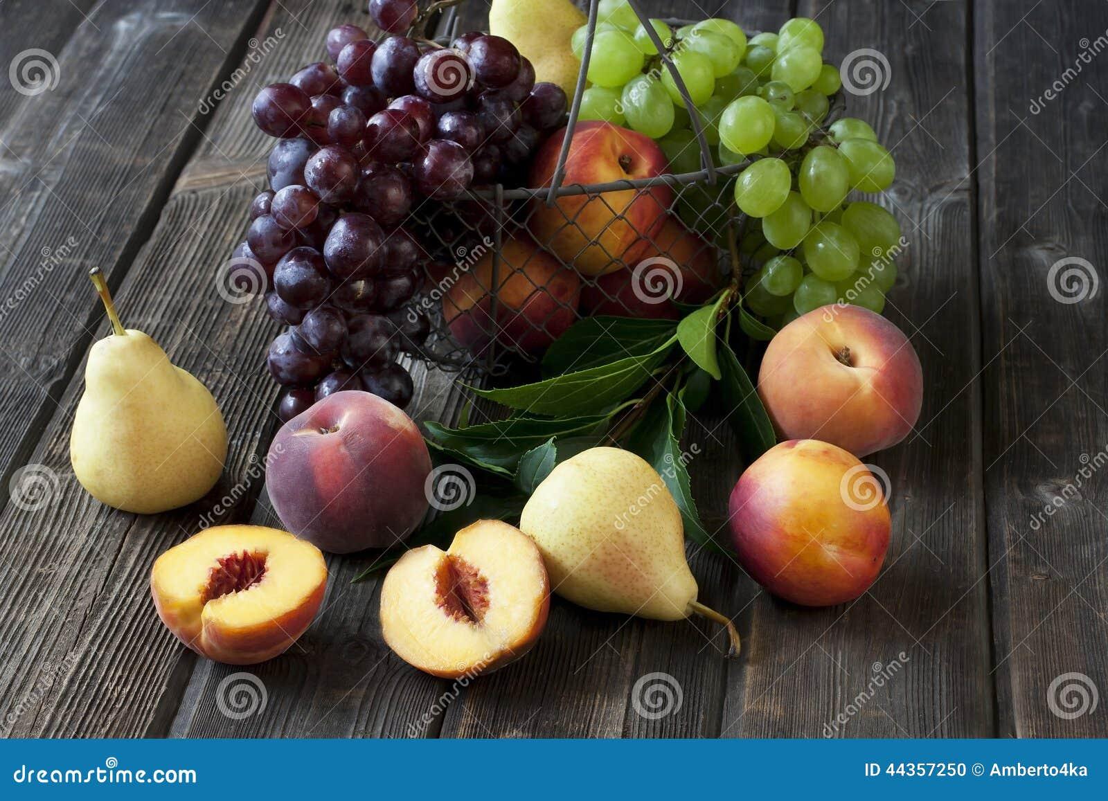 Natura morta con la frutta fresca in canestro di vimini sulla tavola di legno