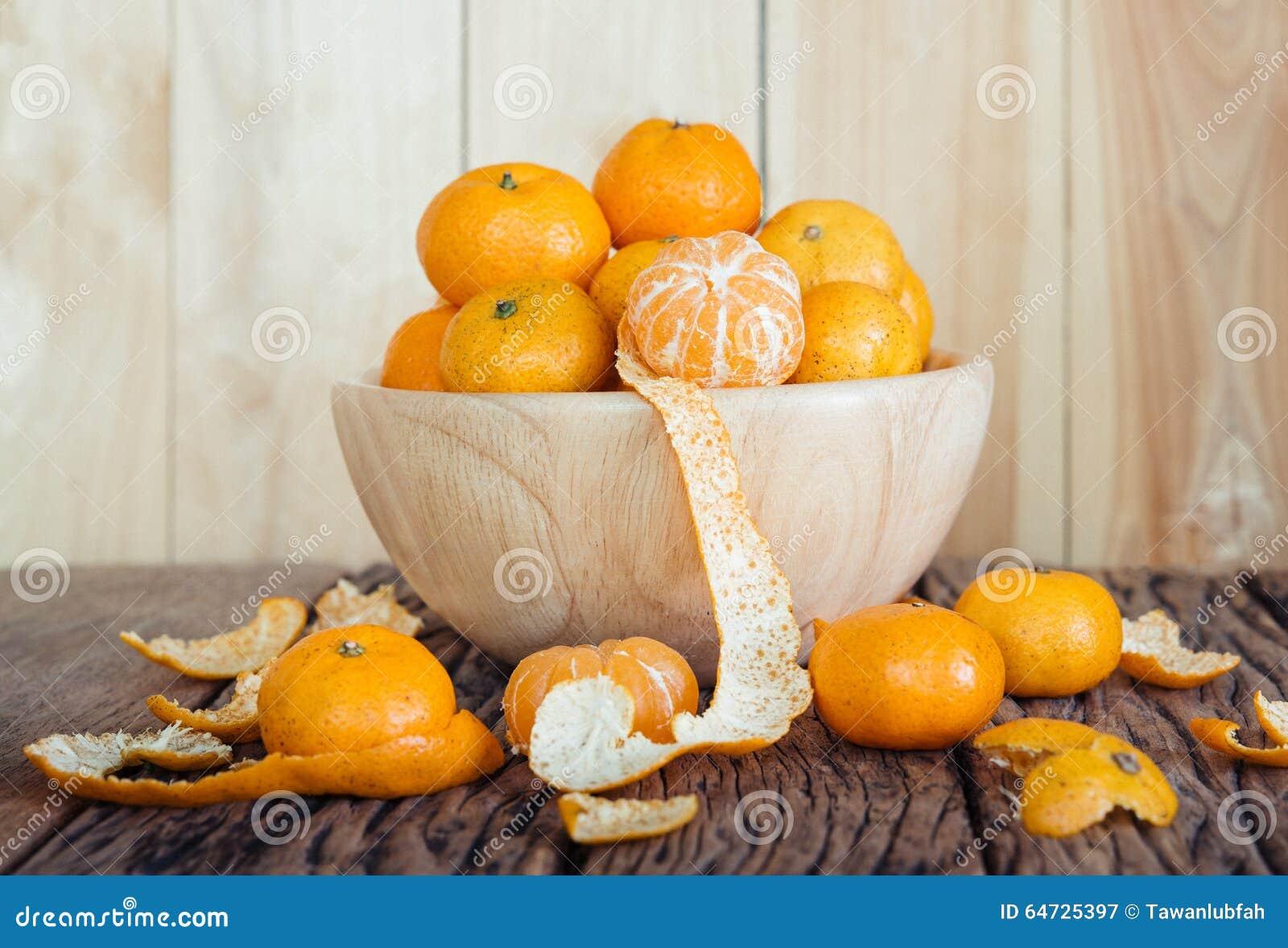 Natura morta di frutta arancio in ciotola su vecchio fondo di legno