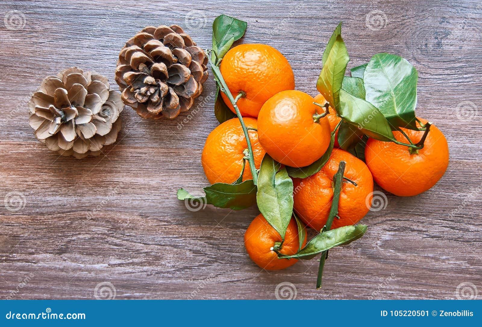 Natura morta di vacanza invernale dei mandarini freschi con le pigne sulla tavola di legno Vista superiore