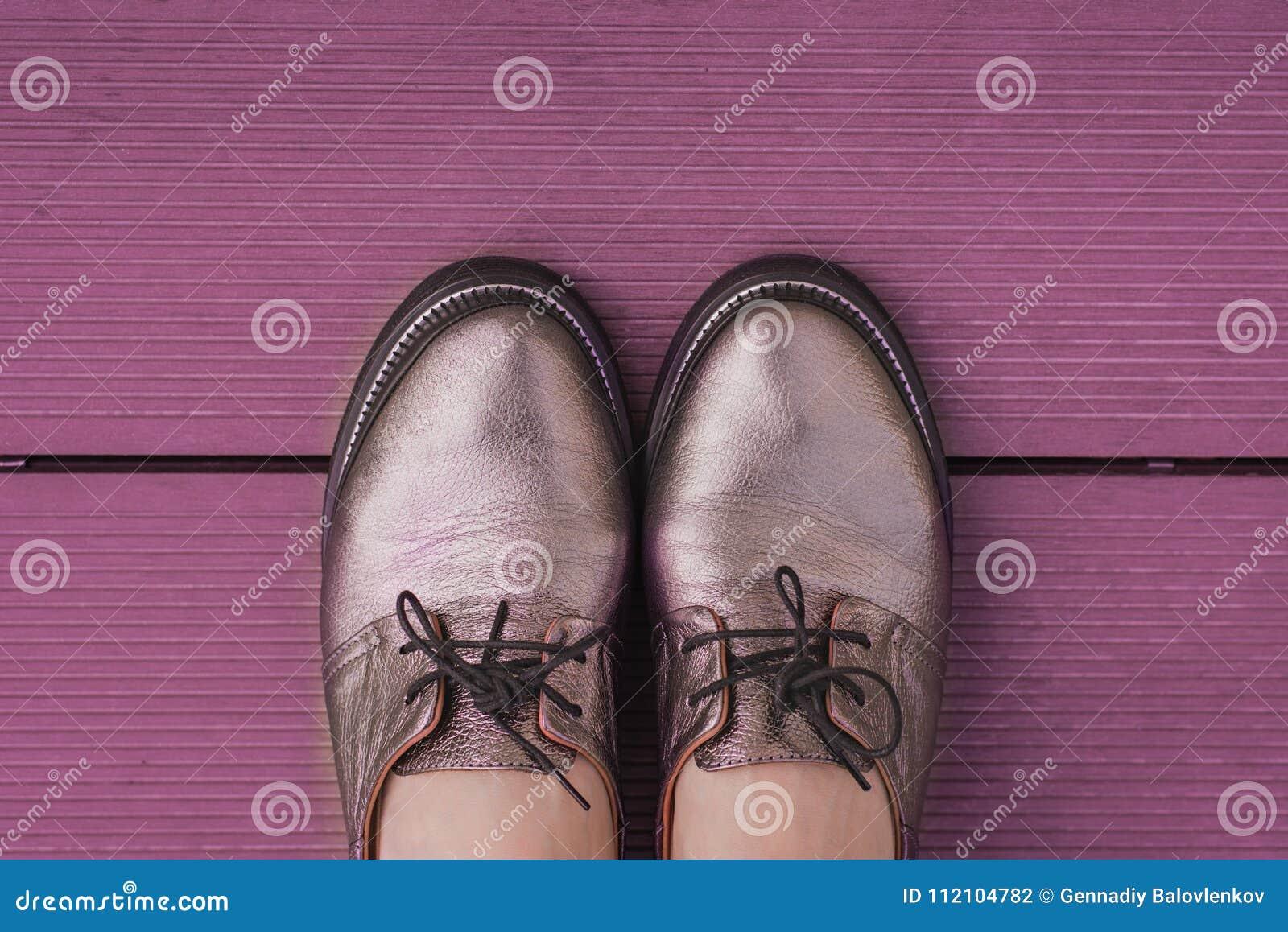 Natura morta in scarpe di cuoio alla moda del ` s delle donne di colore porpora con i pizzi su un bordo di legno porpora