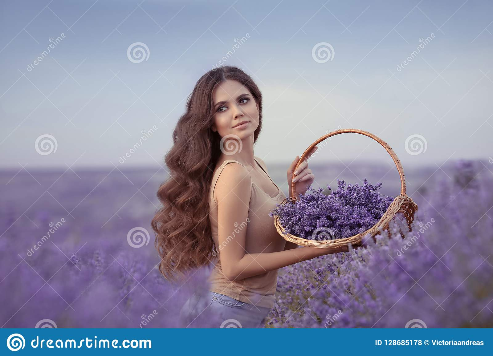 Natural beauty. Beautiful provence woman with basket flowers harvesting in lavender field at sunset. Attractive pretty girl with