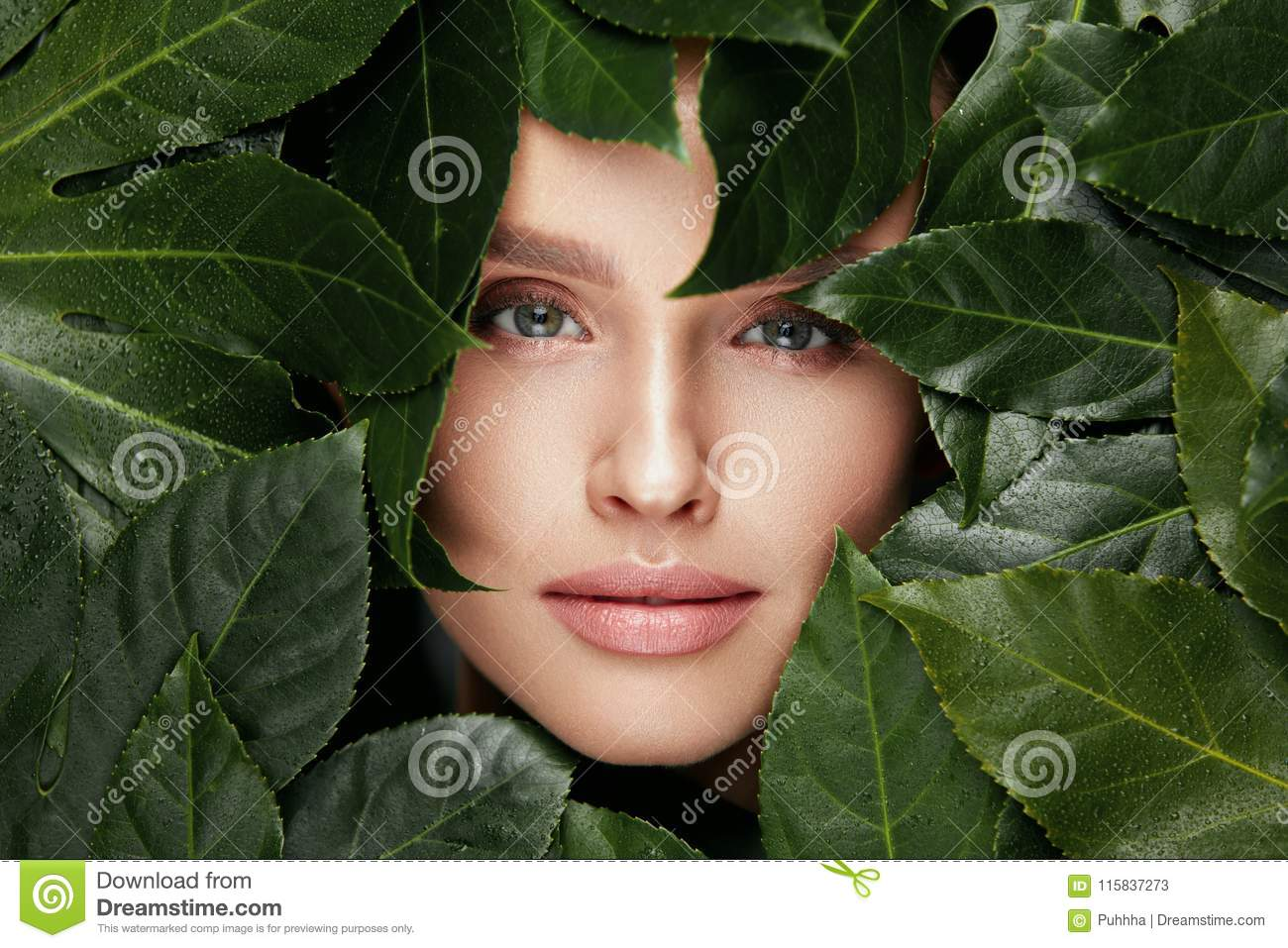 Natural Beauty. Beautiful Woman Face In Green Leaves.