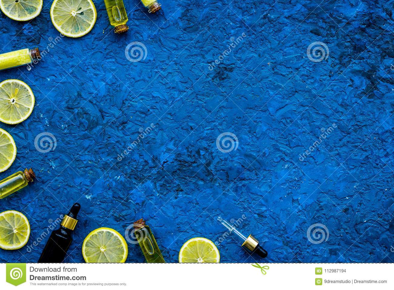 Natural citrus cosmetics. Spa oil near lemon on blue background top view mock-up
