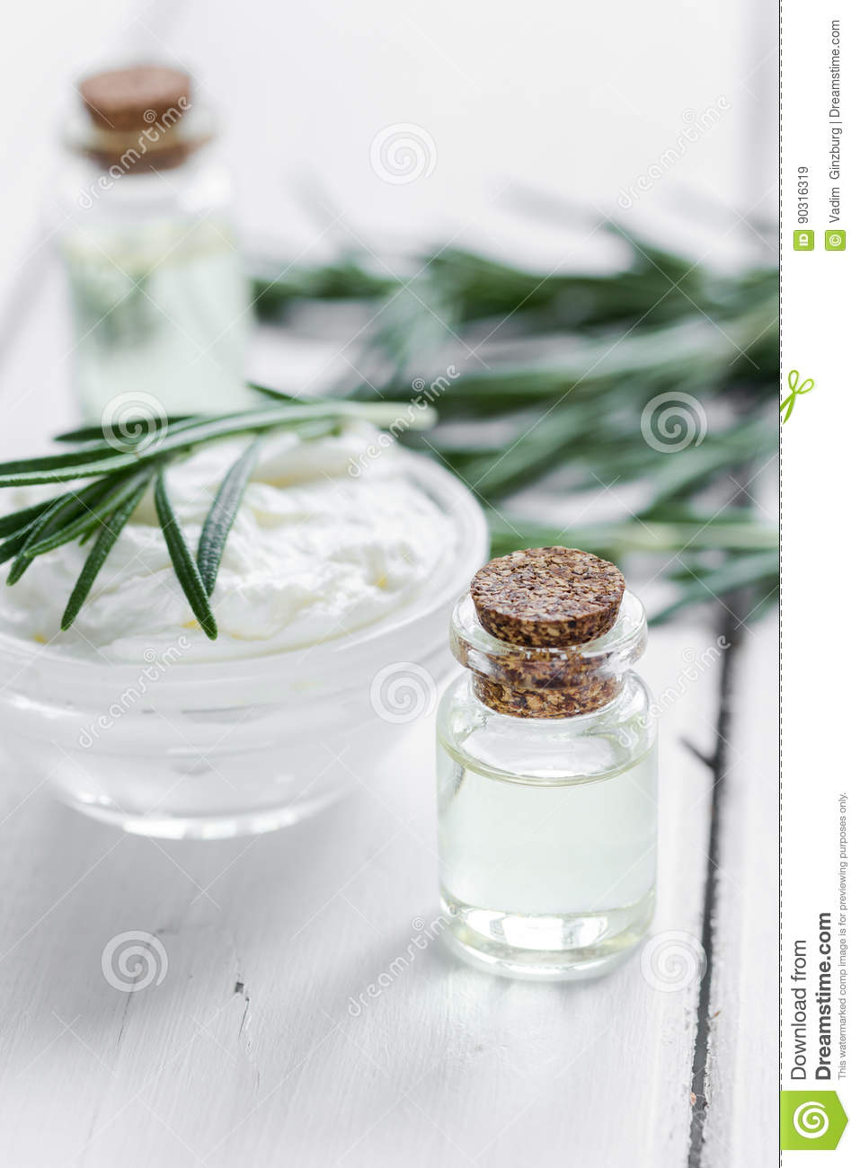 Natural essential aroma oil with rosemary on wooden table background