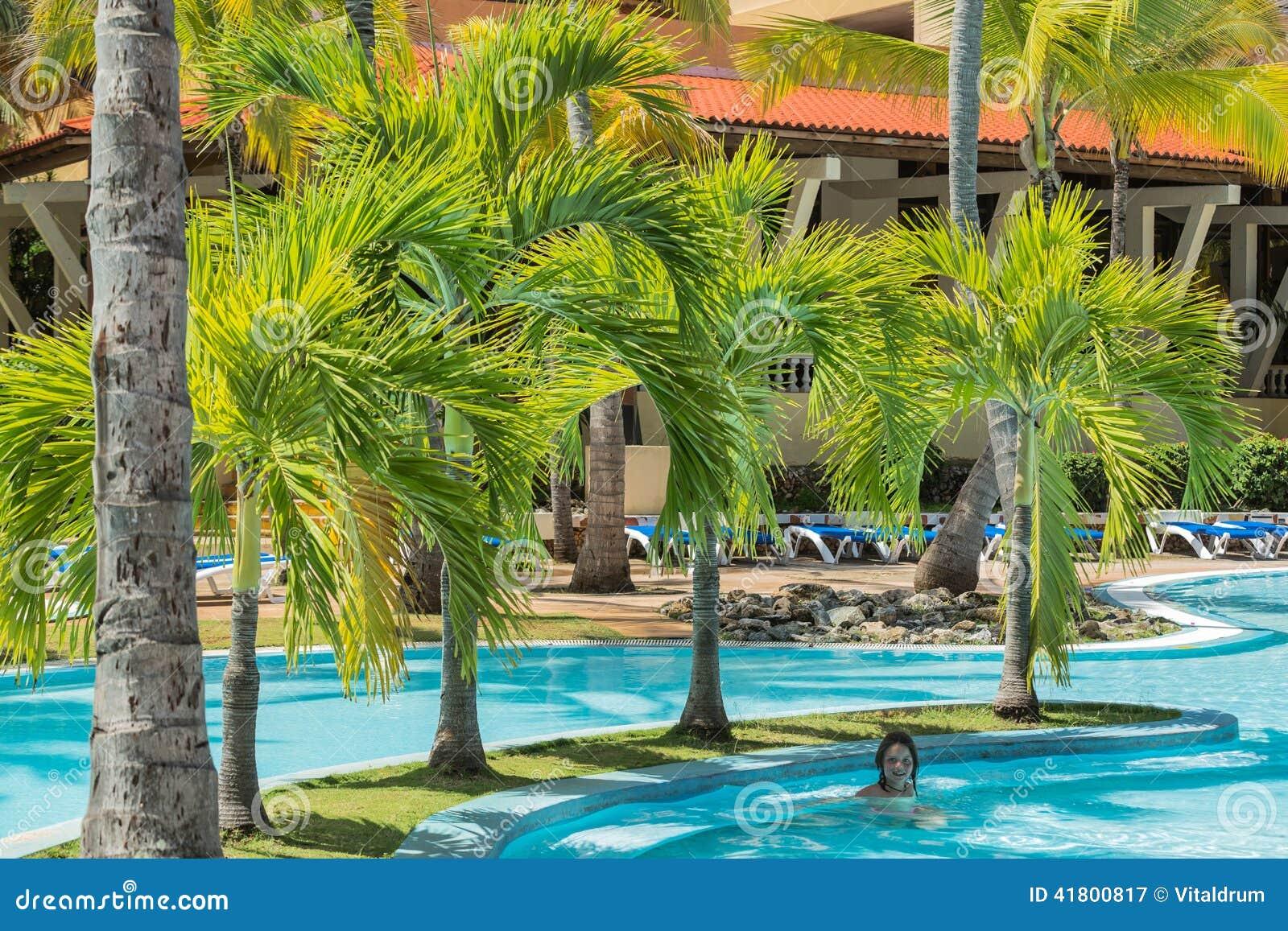 Natural fluffy palm tree garden with little girl swimming for Piscine jardin lescar
