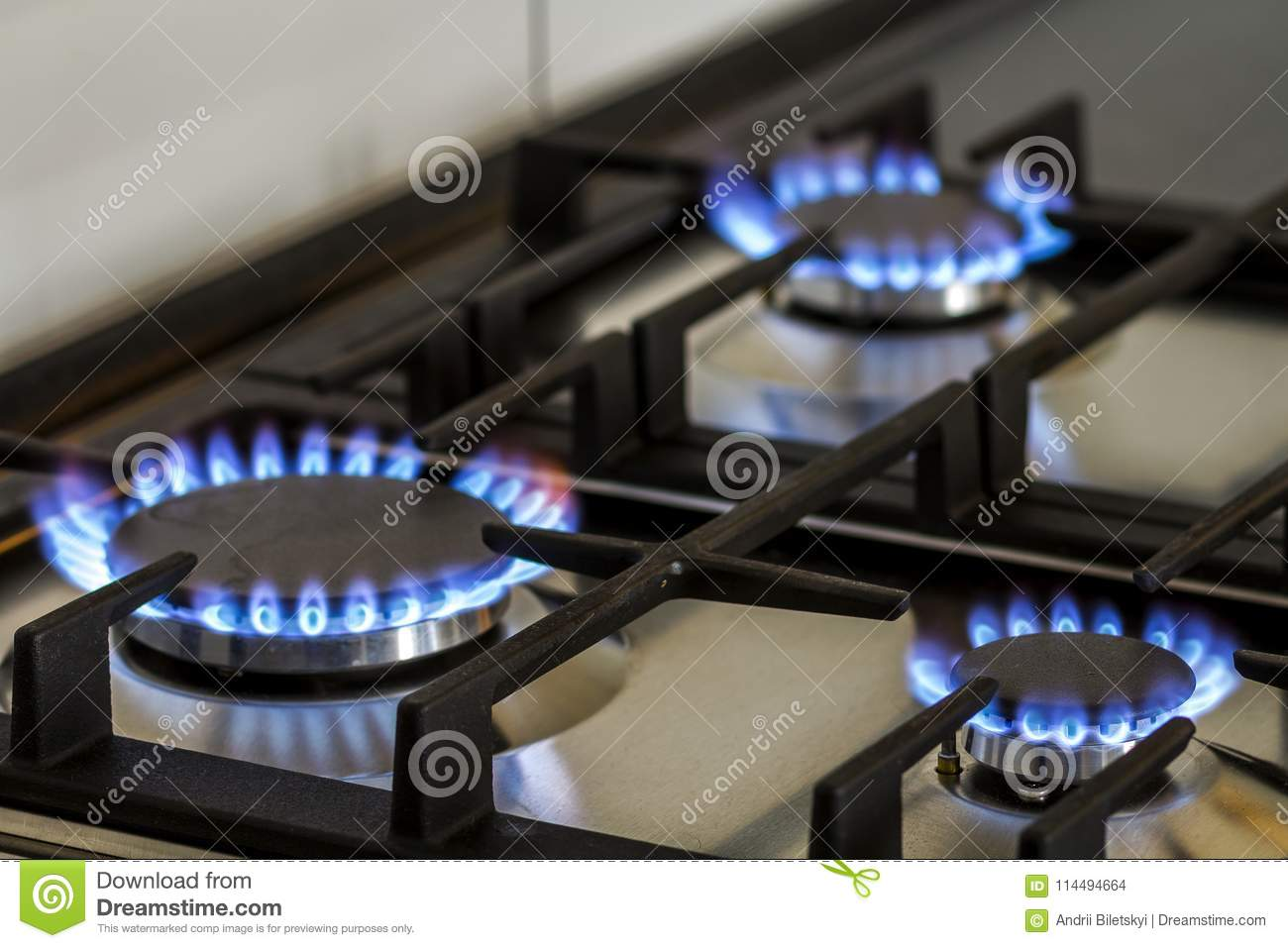 Natural gas burning on kitchen gas stove in the dark. Panel from