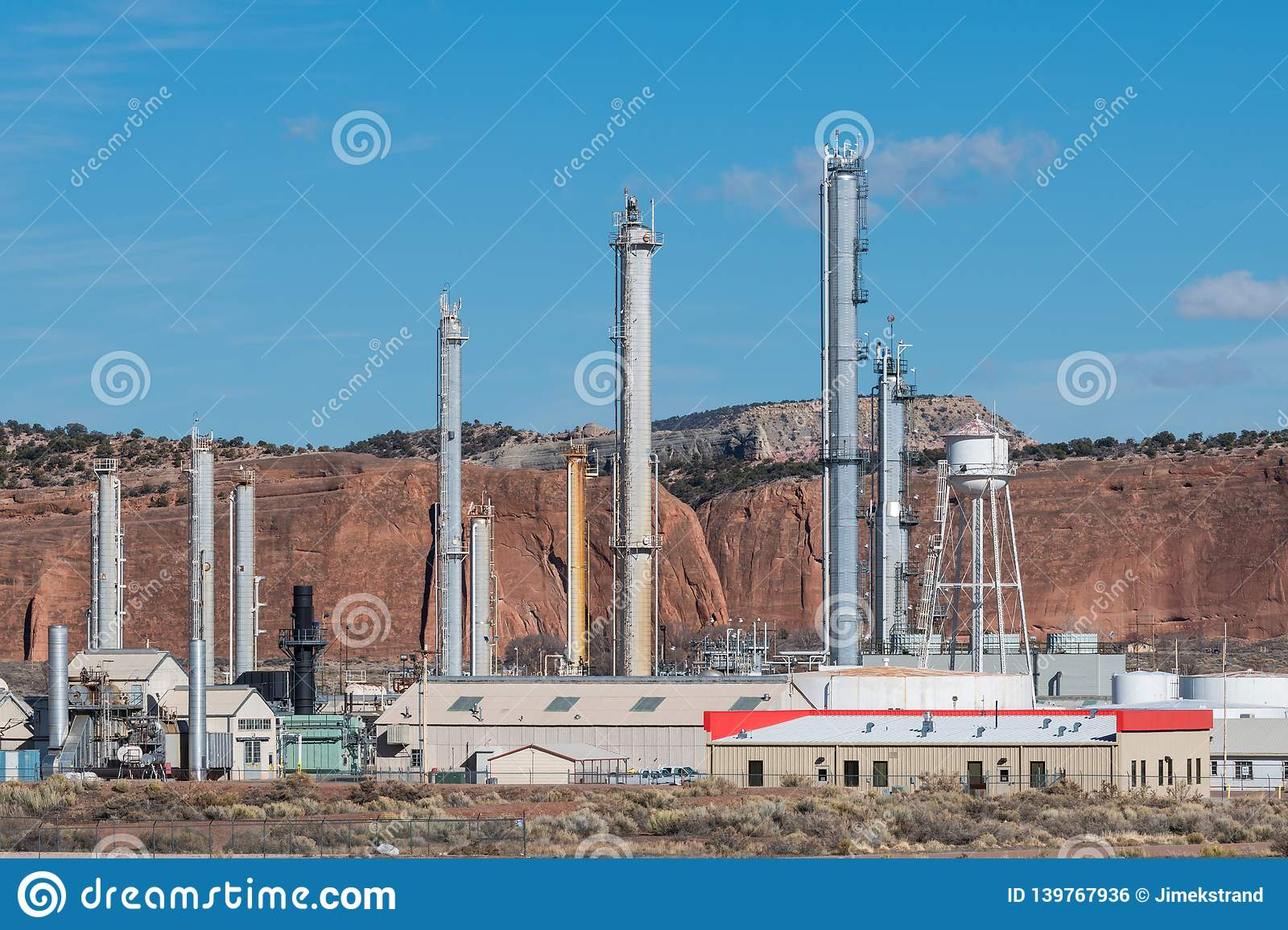 A natural gas refinery contrasted with the natural red rock landscape of the southwestern United States
