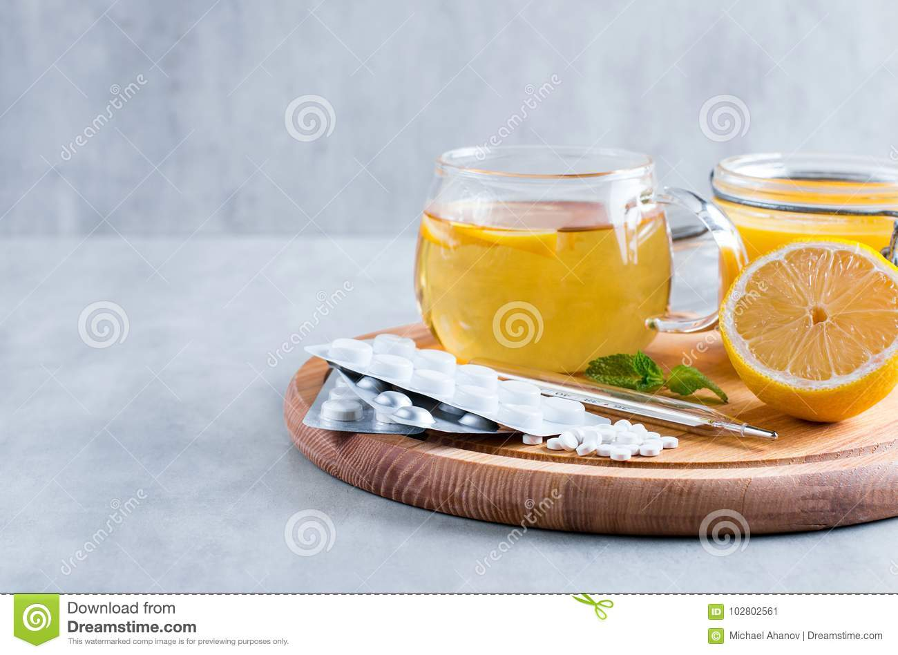 Natural ingredients for cough remedy on wooden table. Lemon, honey, tea, mint and tablets. Top view, space for copy.