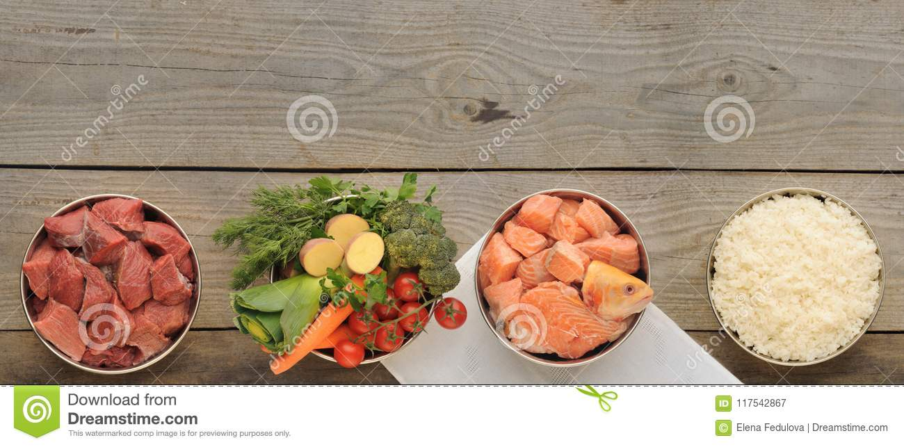 Natural ingredients for dog food in four bowls on old wooden background
