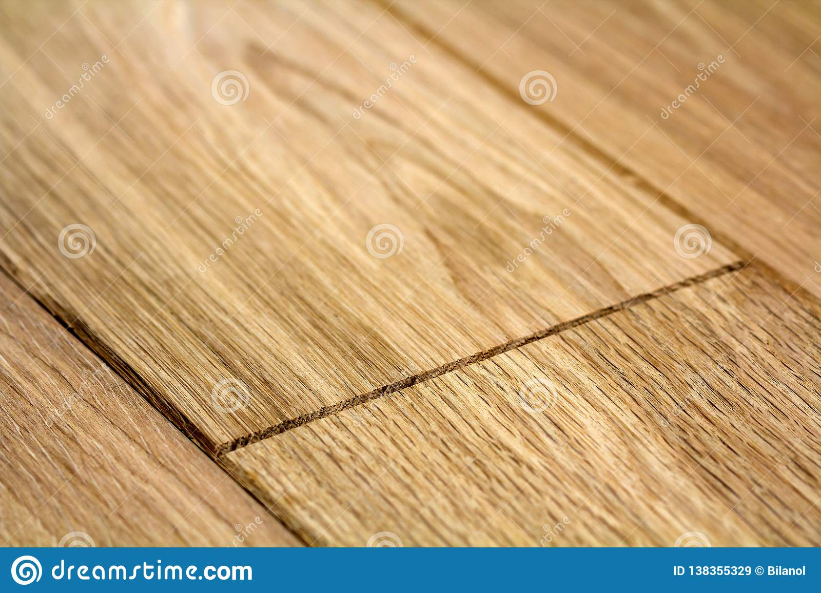 Natural light brown wooden parquet floor boards. Sunny soft yellow texture, copy space perspective background