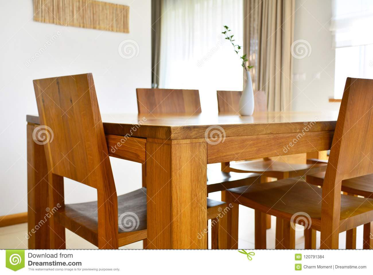 Natural oak wood dining table and chairs in neutral modern inter