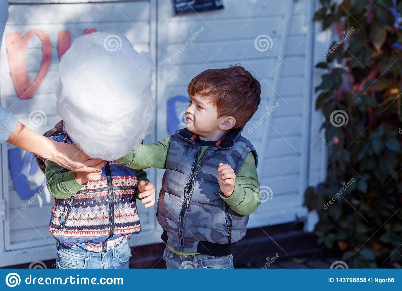 Natural pictures of a happy family of four having fun outsiade and eating sugar floss. A family of four