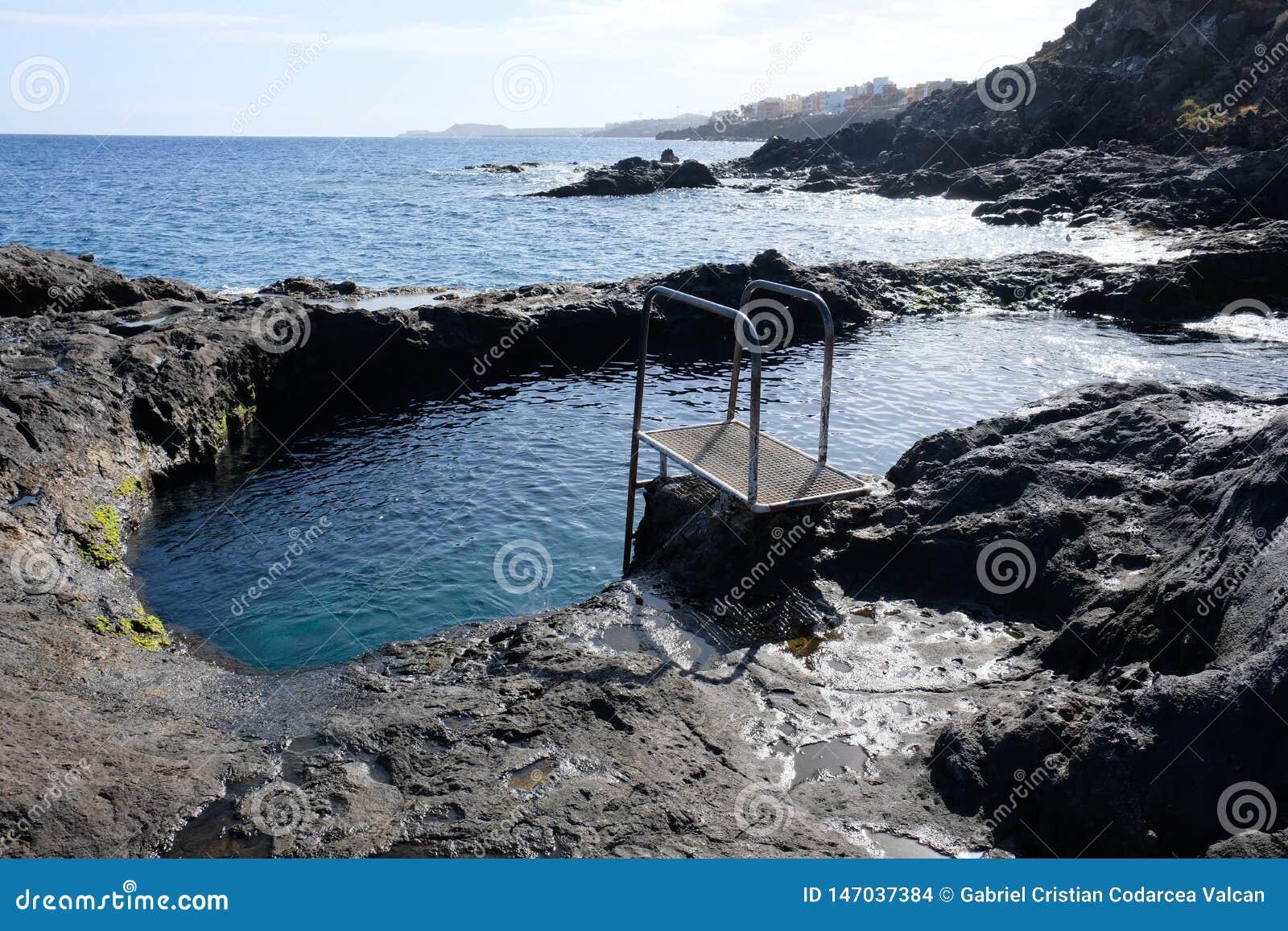 Natural pool on volcanic rocks shore