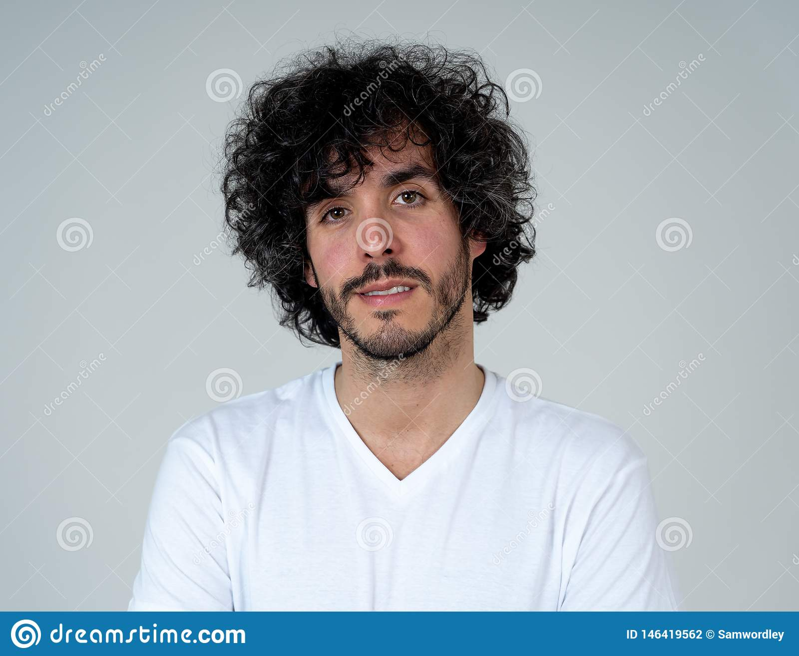 Natural portrait of young attractive man in his 20s looking and posing with neutral face expression