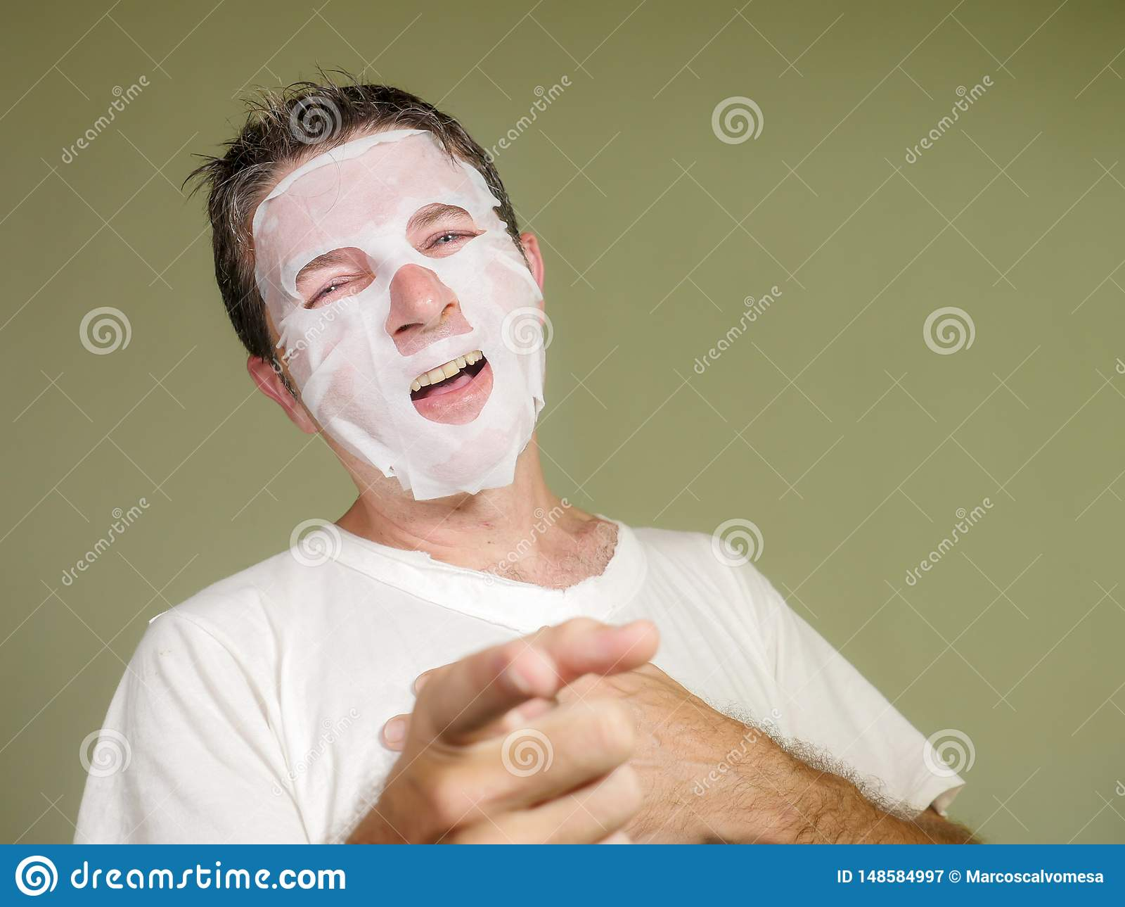 Natural portrait of young happy and funny man applying beauty facial mask looking in the mirror laughing cheerful finding himself