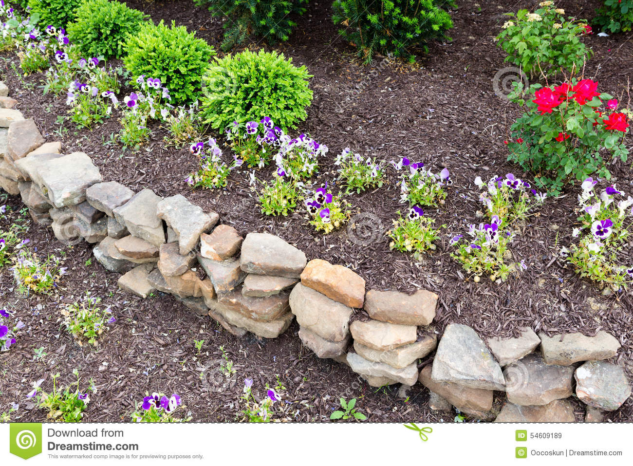 Natural rock retaining wall in a garden stock image for Landscaping rocks and plants