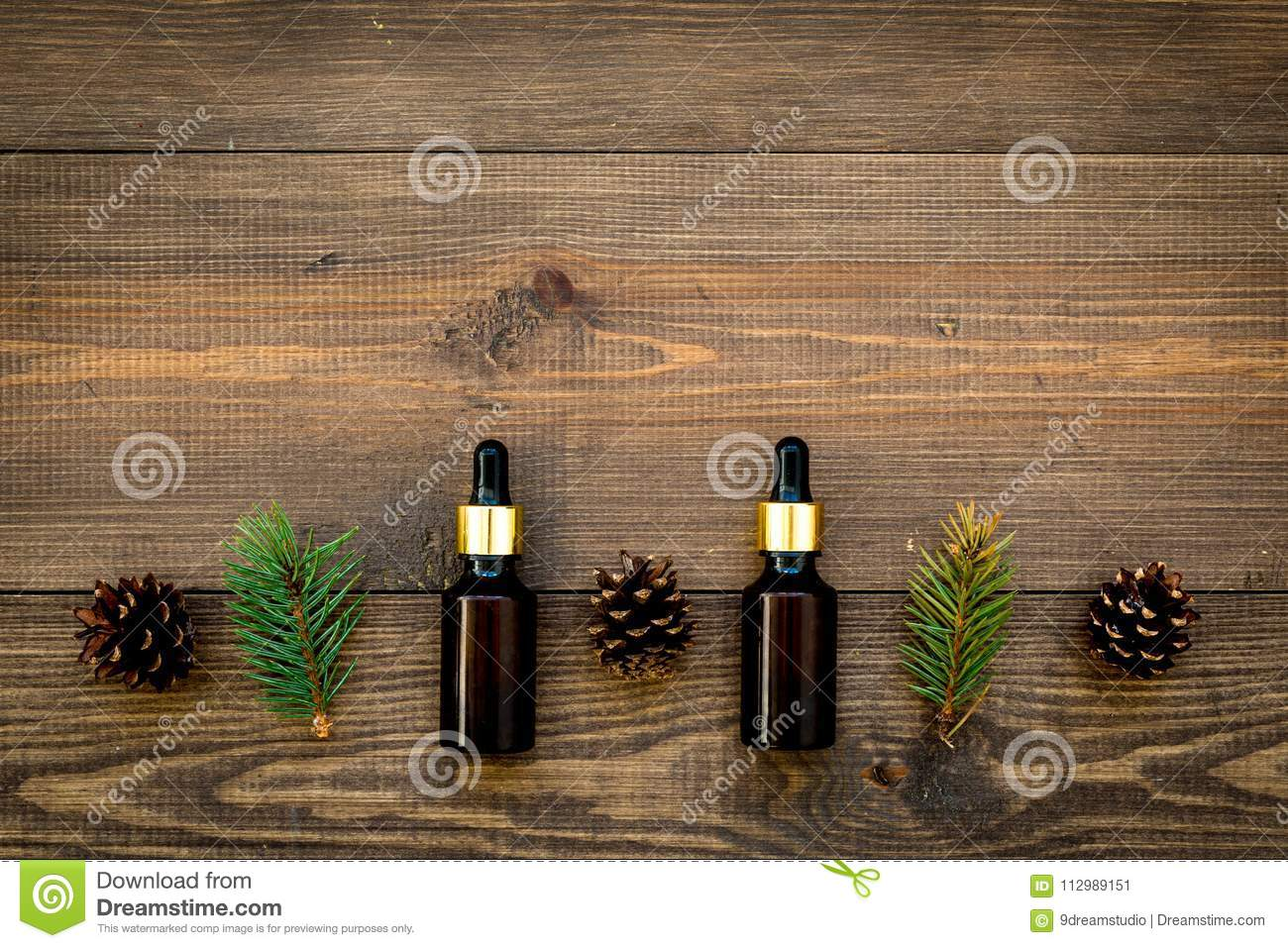 Natural spa cosmetics with pine essential oil for aroma on wooden background top view mock-up