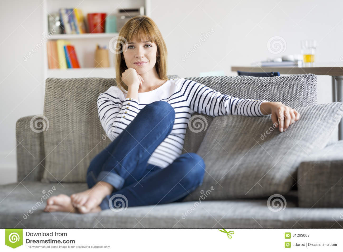 Natural Thirty Year Old Woman Seated On Couch In Modern Home