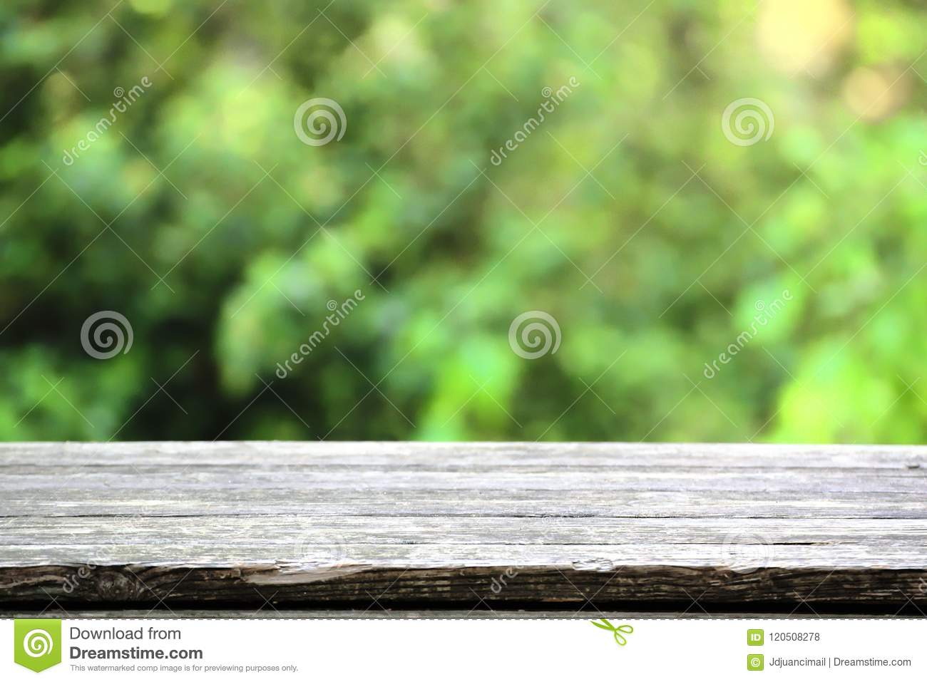 Natural wooden table in a rustic environment against a blured green background. Empty copy space