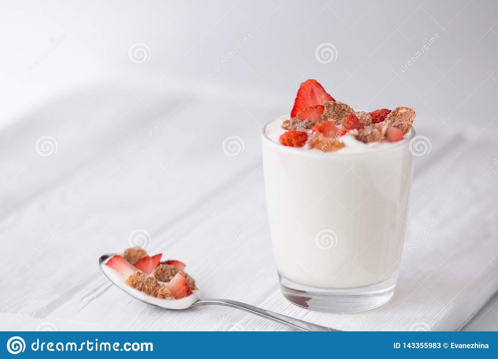 Natural yogurt  with strawberry and multigrain flakes on a white wooden table. Front view