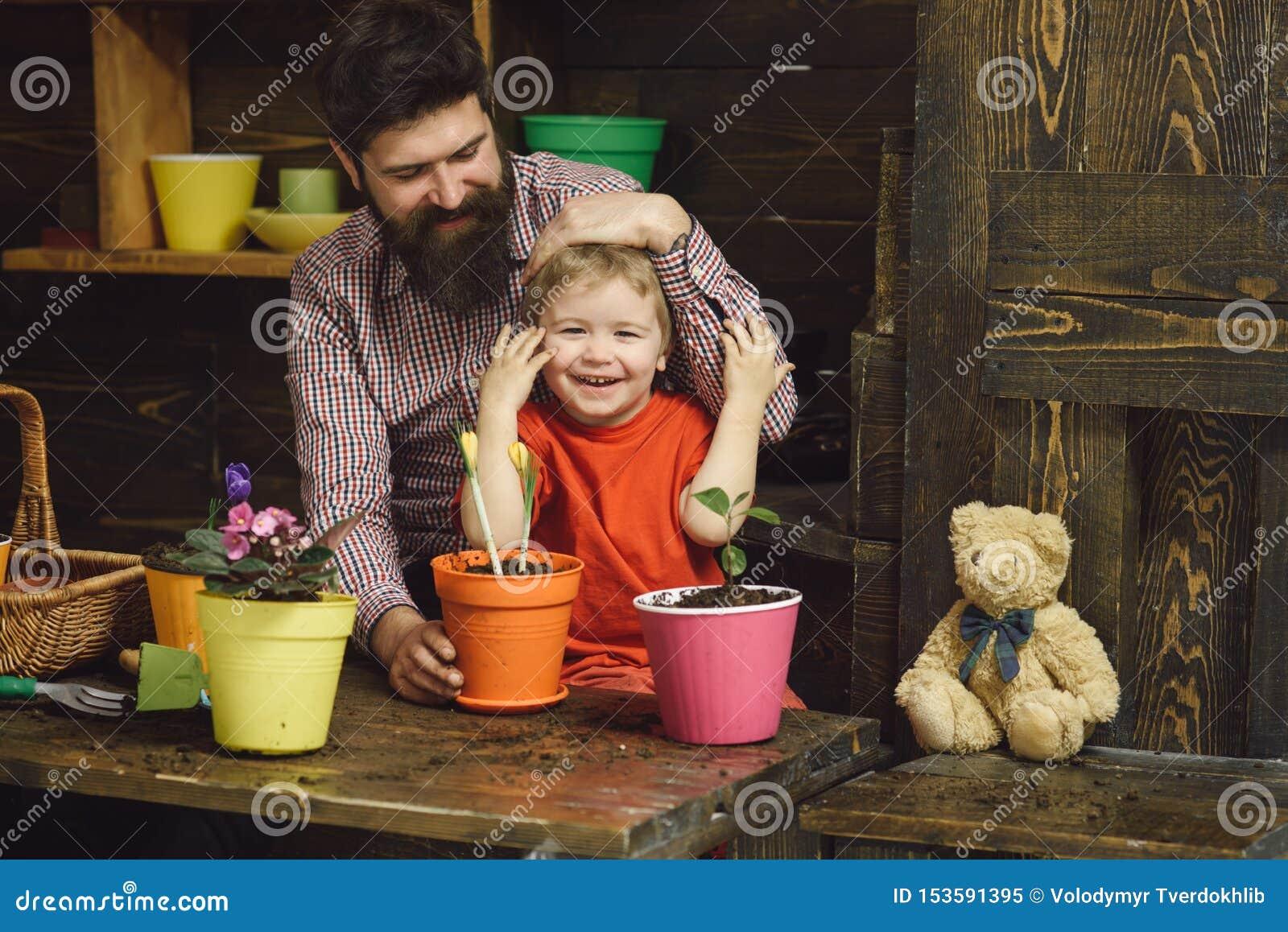 Naturaleza barbuda del amor del ni?o del hombre y del ni?o peque?o D?a de la familia invernadero jardineros felices con las flore