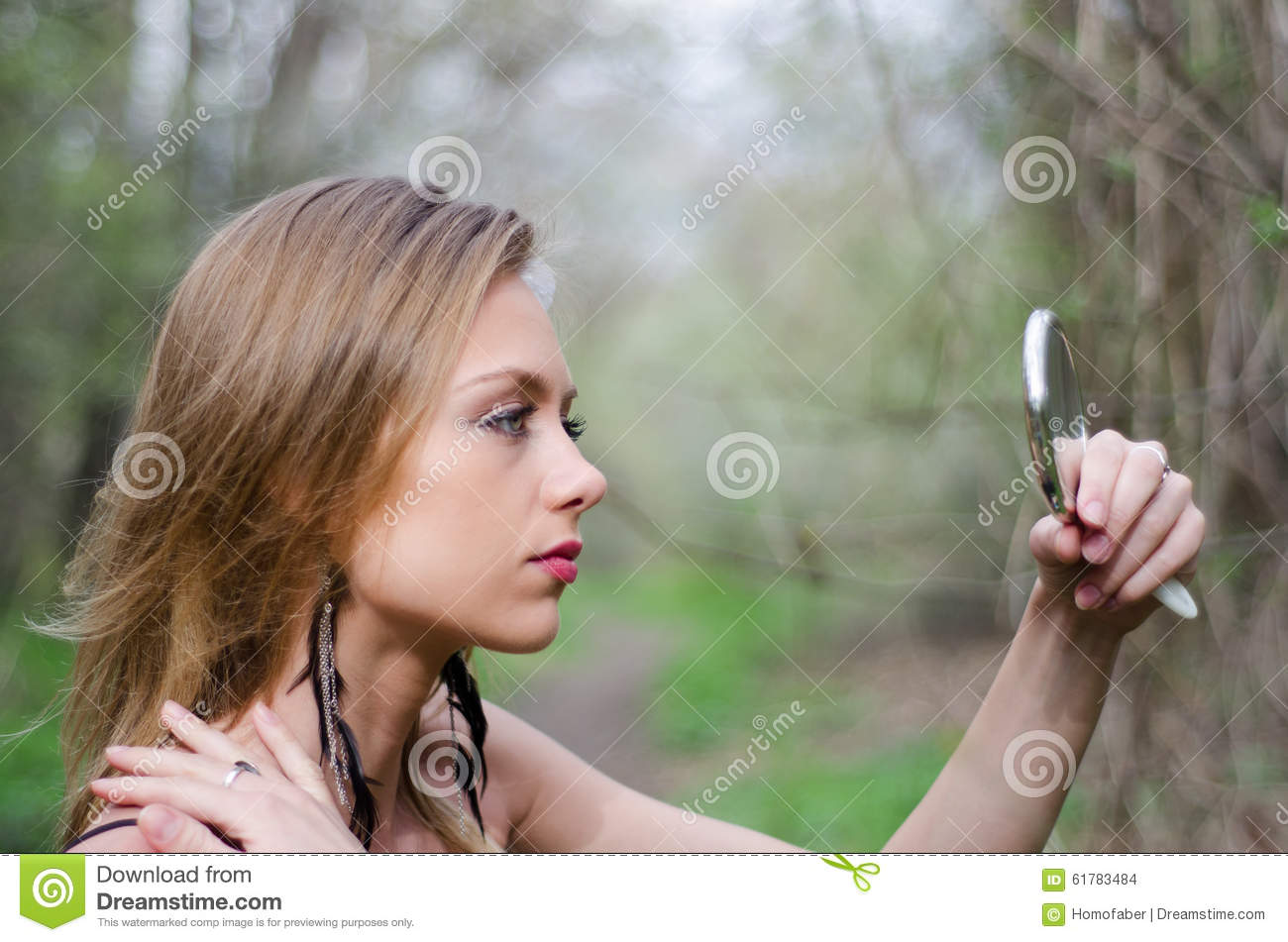 Naturally Beautiful Young Blond Woman In Nature Holding A Mirror