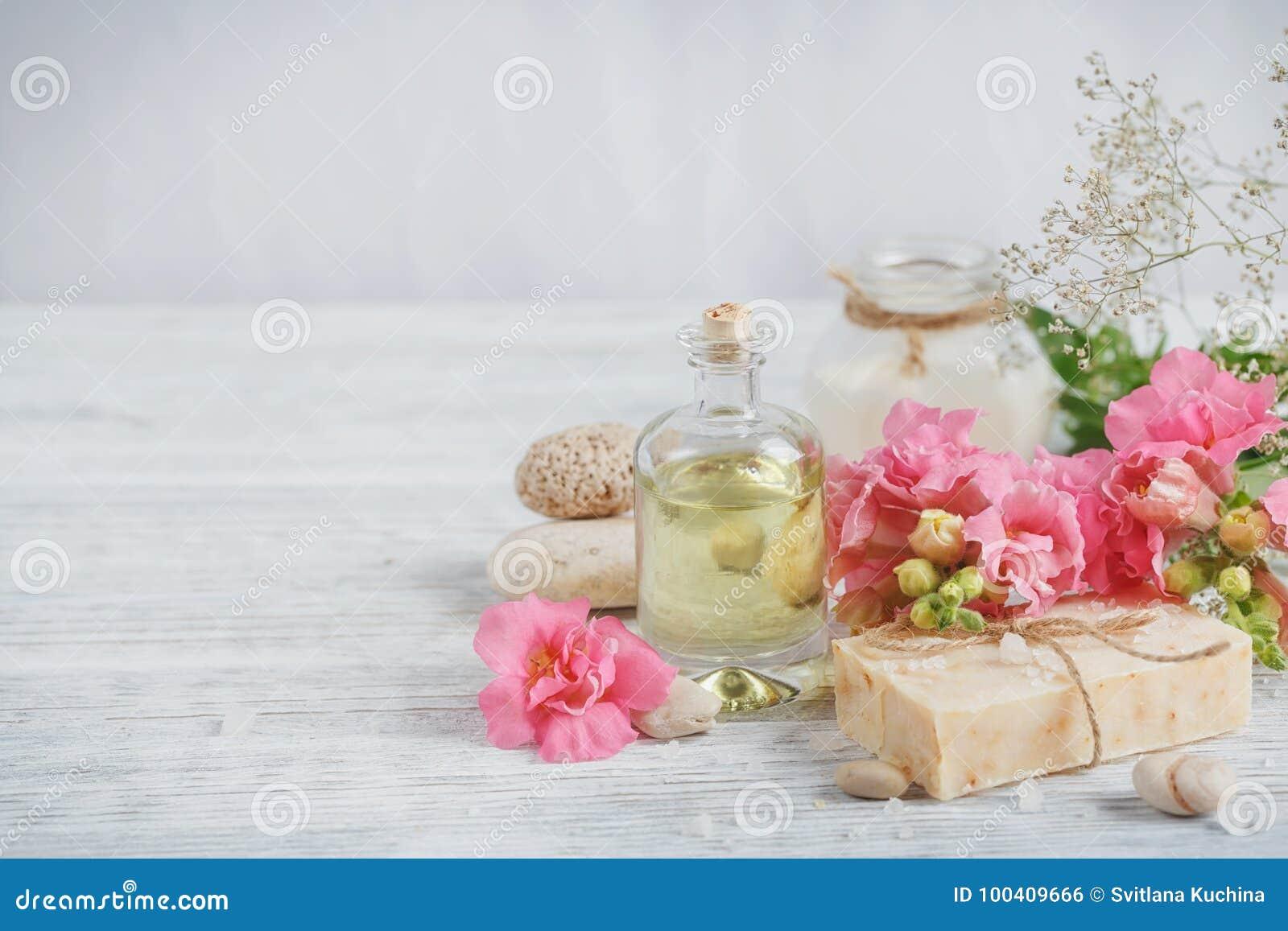 Naturalny handmade mydło, aromatyczny olej i kwiaty na biały drewnianym,