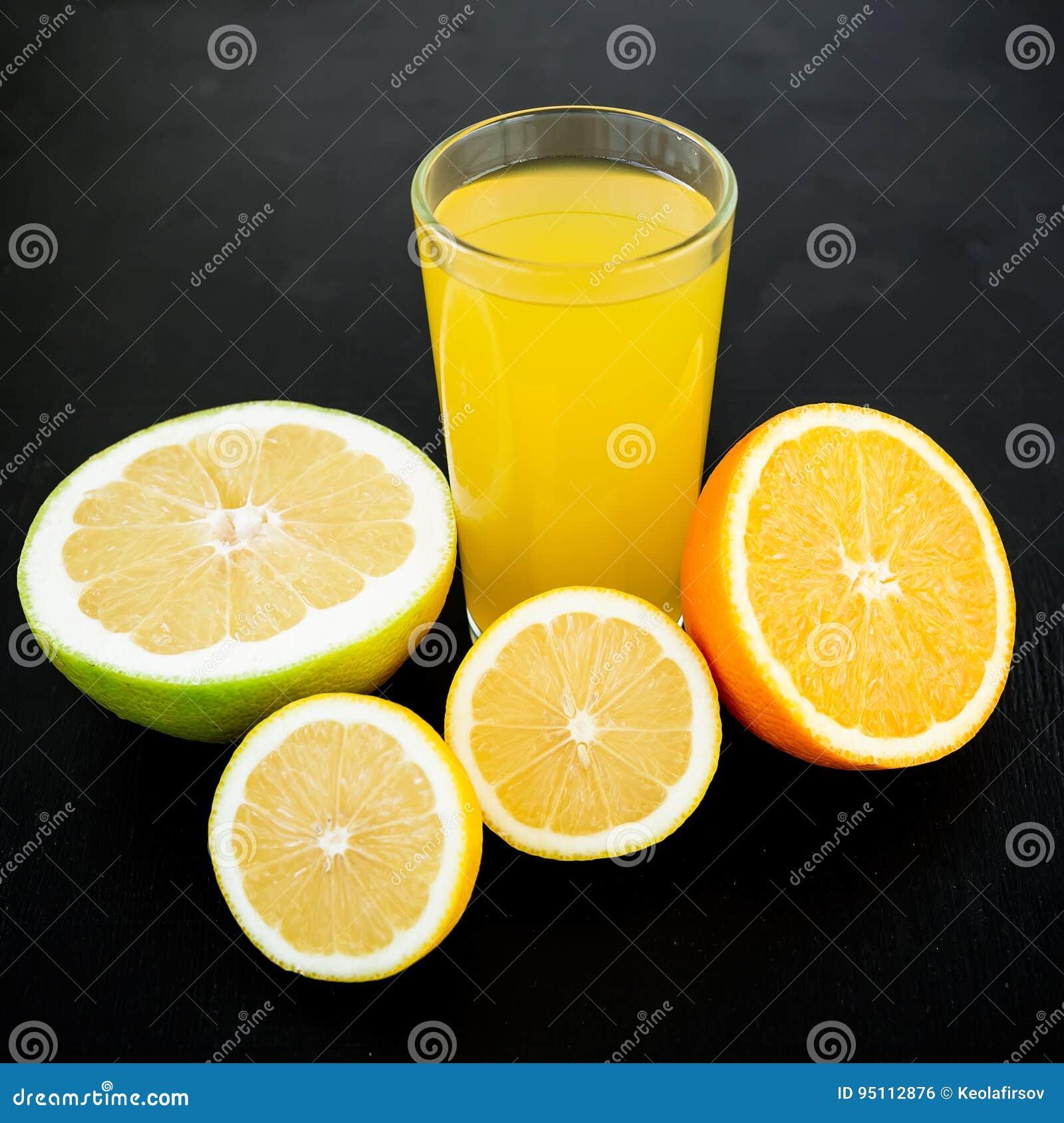 Naturalny smakowity sok robić cytryna, pomarańcze, mandarynka i sweetie, na czarnym tle Owocowy pojęcie