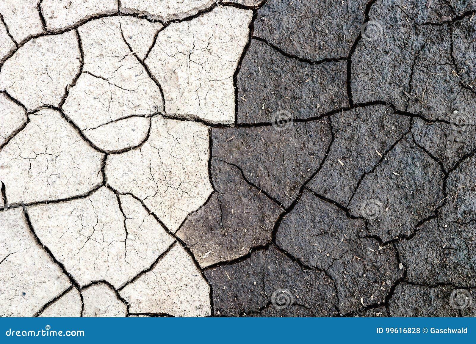 Naturbakgrund, gräns av torr och våt sprucken gyttja Begrepp av motsatser, mörker och ljus