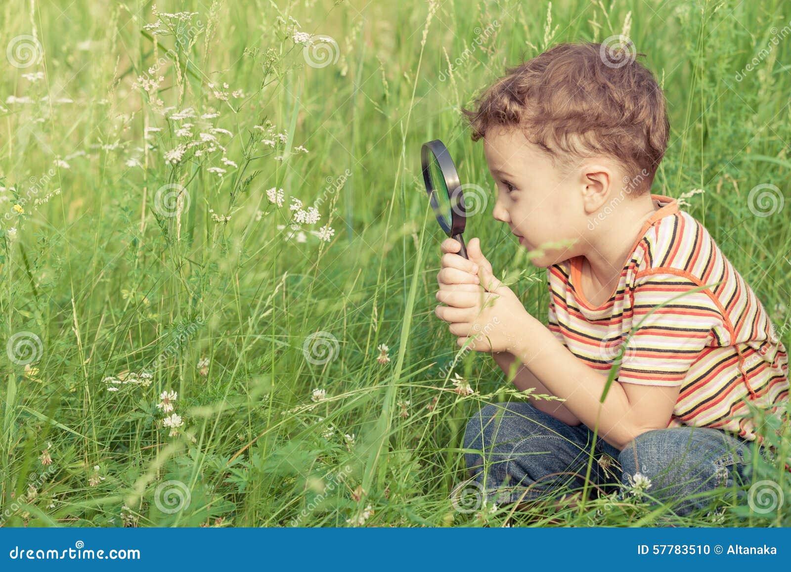 Nature l explorant heureuse de petit garçon avec la loupe