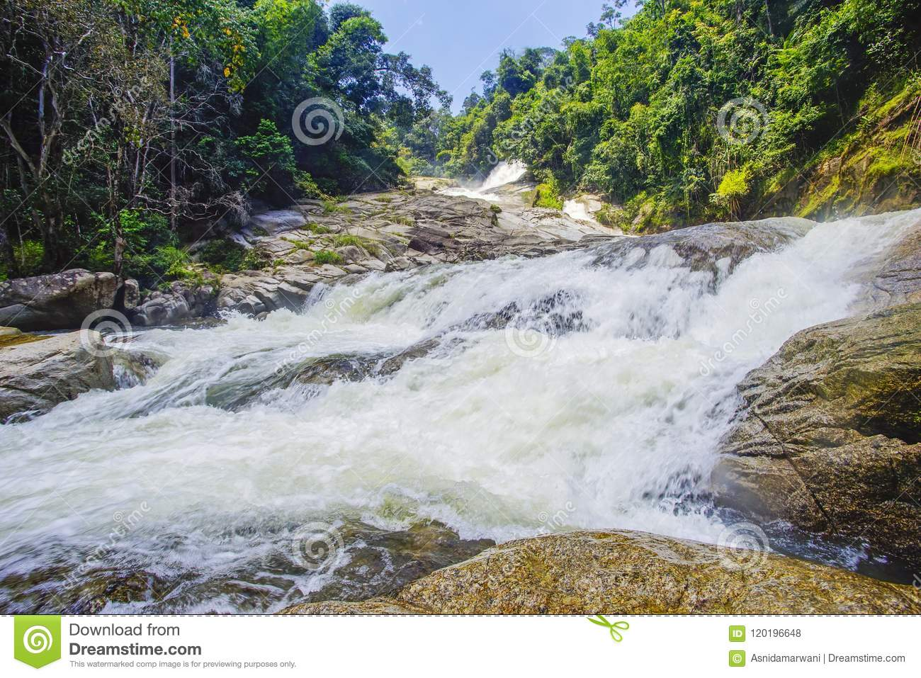 Nature landscape of waterfall cascade during bright day.