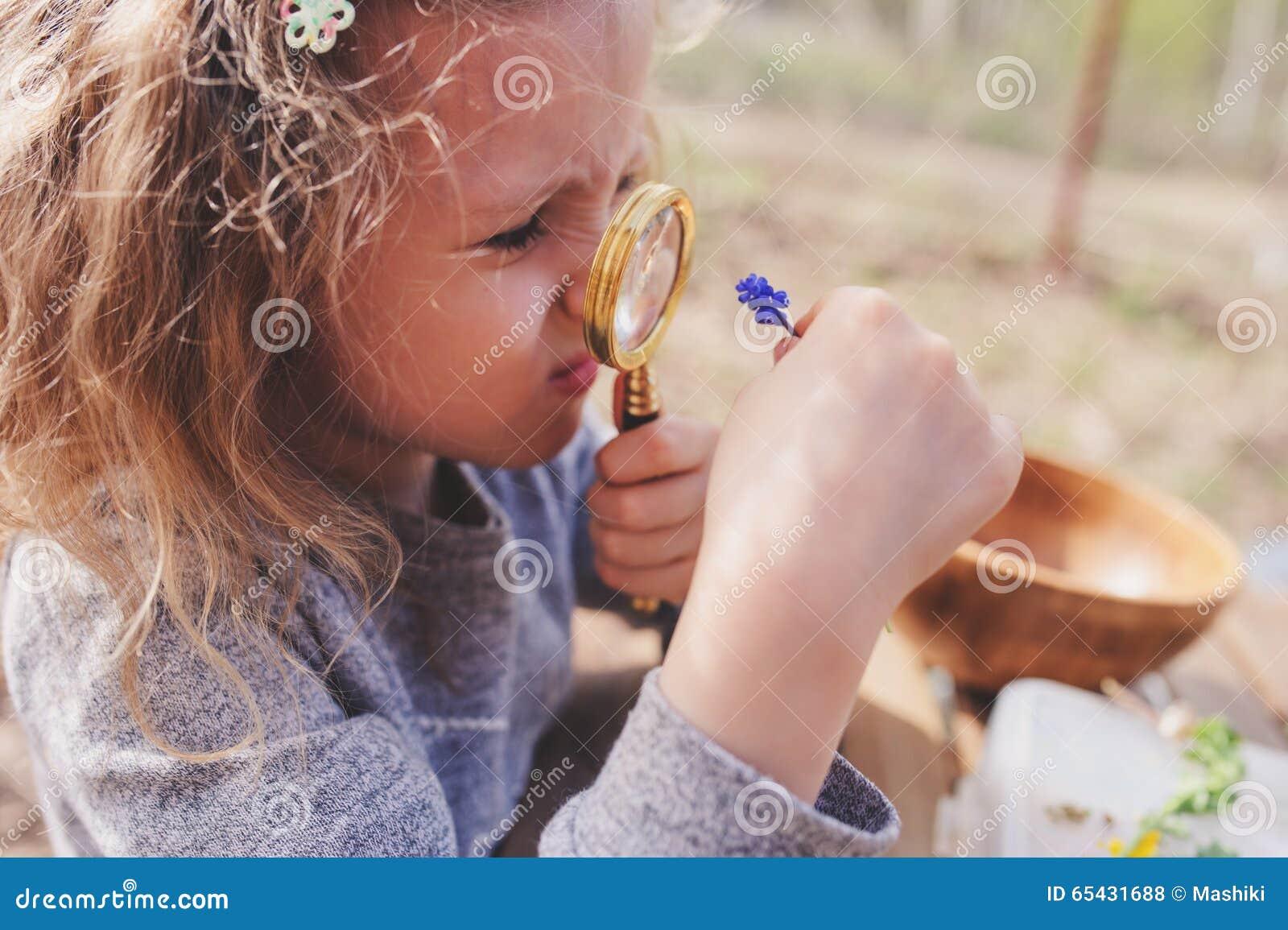 A natureza de exploração da menina da criança na floresta adiantada da mola caçoa a aprendizagem amar a natureza Crianças de ensi