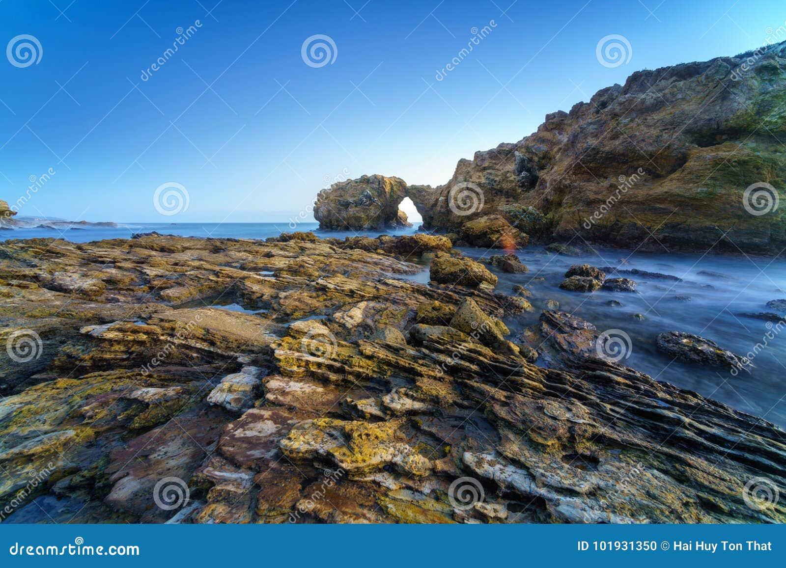 Naturligt vagga bågen, klippan och stranden