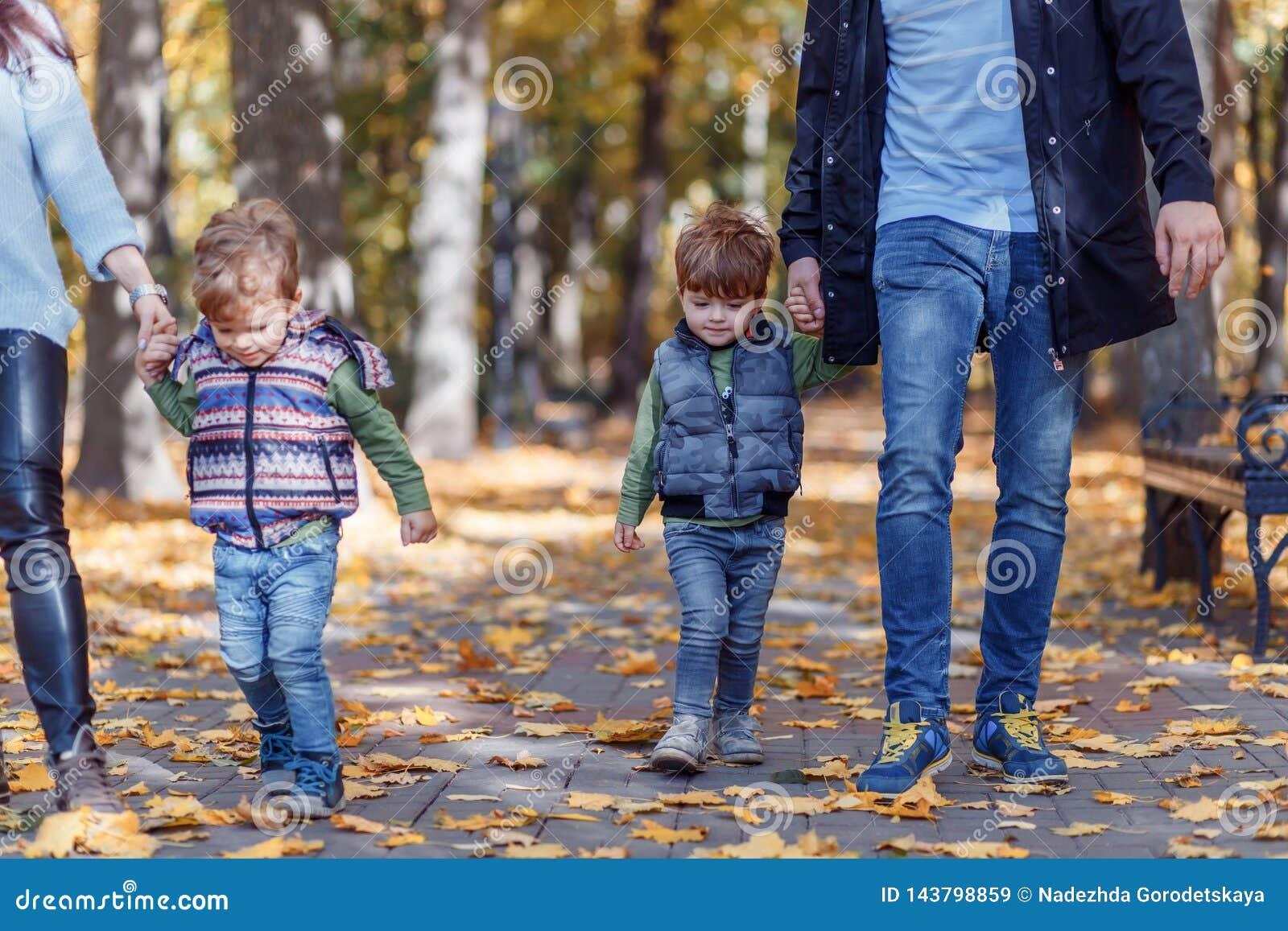Natuurlijke beelden van een gelukkige familie van vier die pret outsiade op een zonnige de herfstdag hebben Samenhorigheid en gel