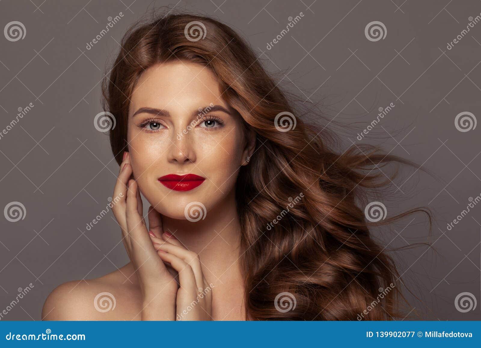 Natuurlijke Schoonheid Authentieke roodharigevrouw met blazend krullend haar en rode lippenmake-up, perfect gezicht