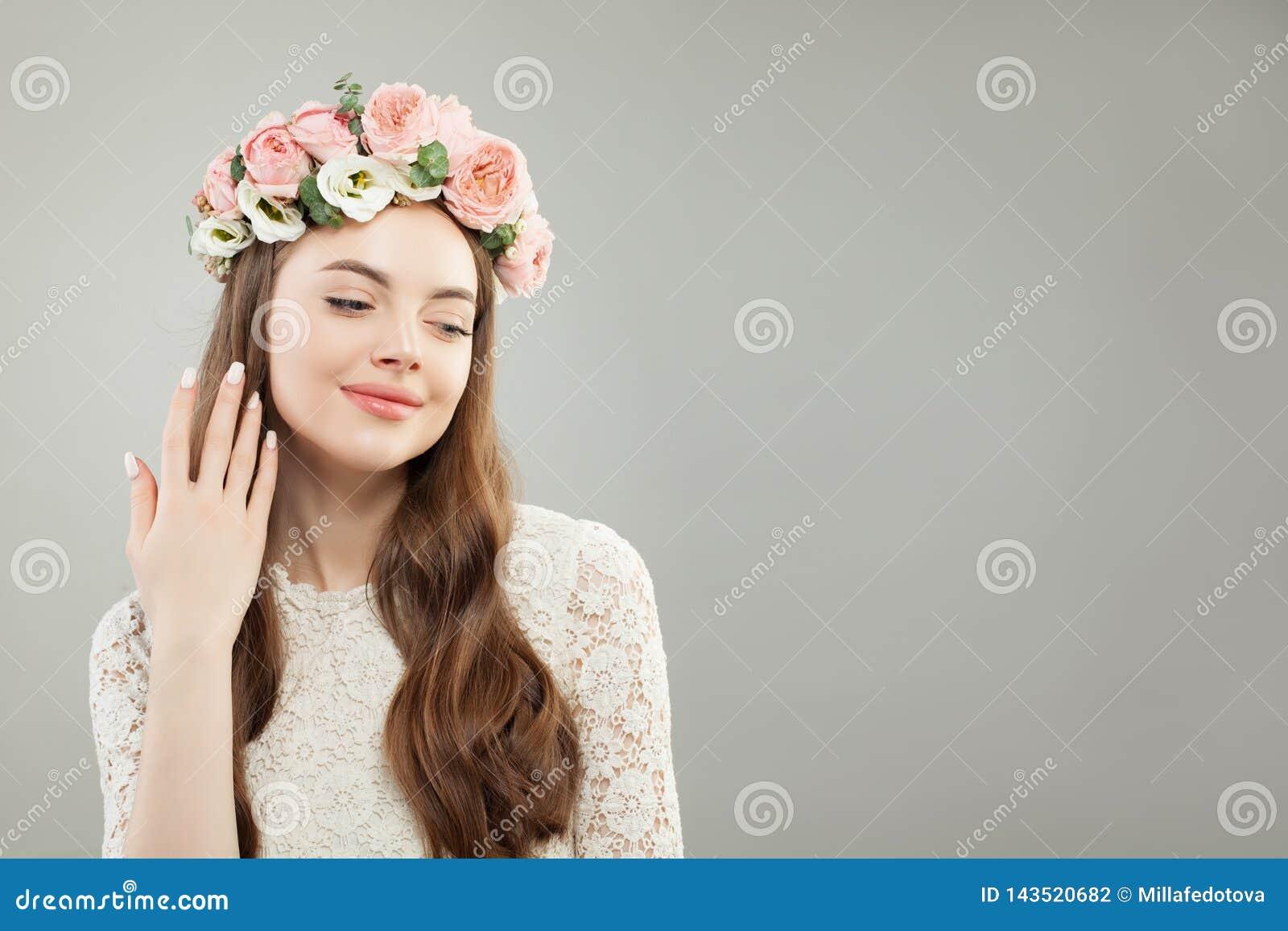 Natuurlijke Schoonheid Mooi ModelWoman met Lang Krullend Haar, Gezonde Huid, Natuurlijke Naakte Make-up en Bloemen