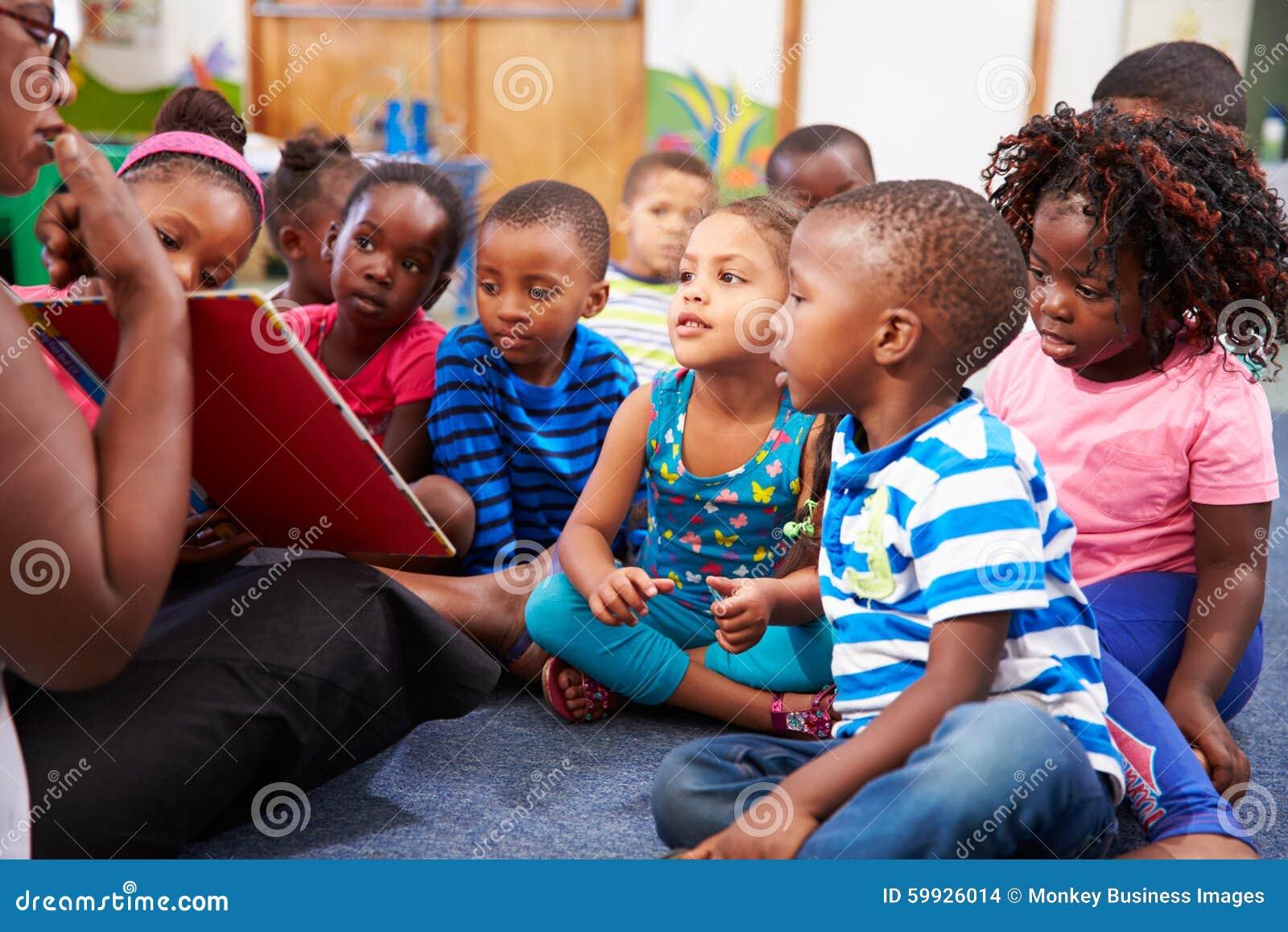 Nauczyciel czyta książkę z klasą preschool dzieci